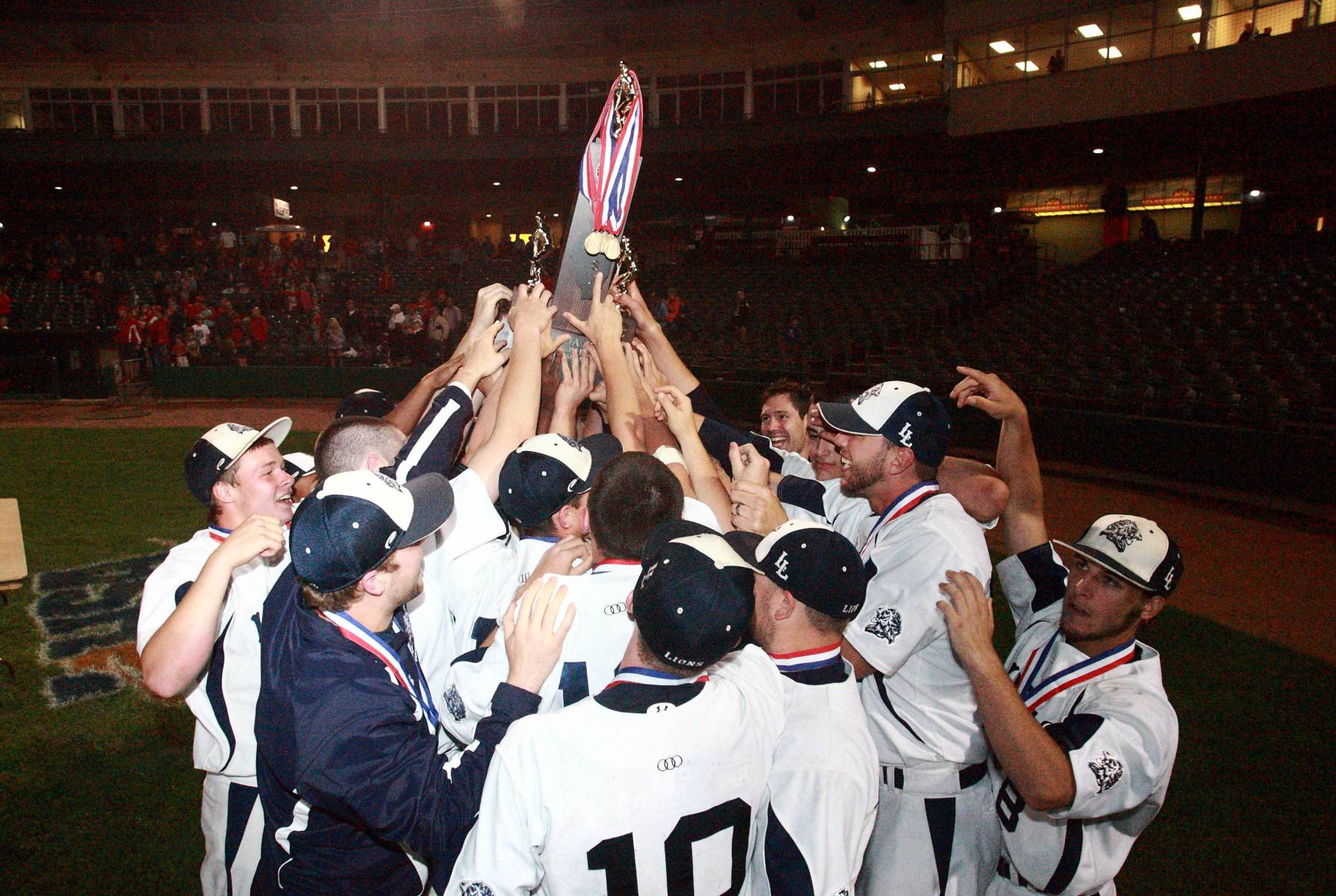 Members of the 2013 Lions baseball team celebrate their new state baseball trophy at the IHSA state baseball tournament in June.