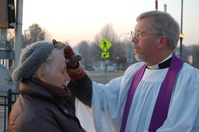 The Rev. Bill Nesbit of St. Charles Episcopal Church imparts ashes on the forehead of a morning commuter at the Geneva Metra station on Ash Wednesday in 2013.