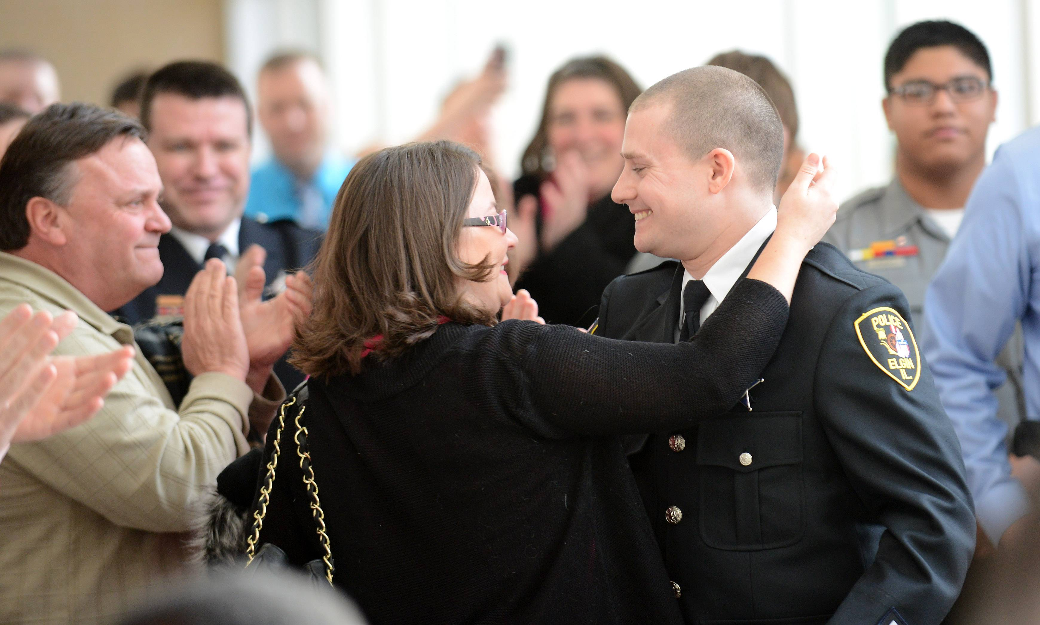 Rick West/rwest@dailyherald.com Officer Steven Alcorn gets congratulations from his wife Larissa after being named Rookie of the Year during the Elgin Police Department annual awards ceremony Monday.
