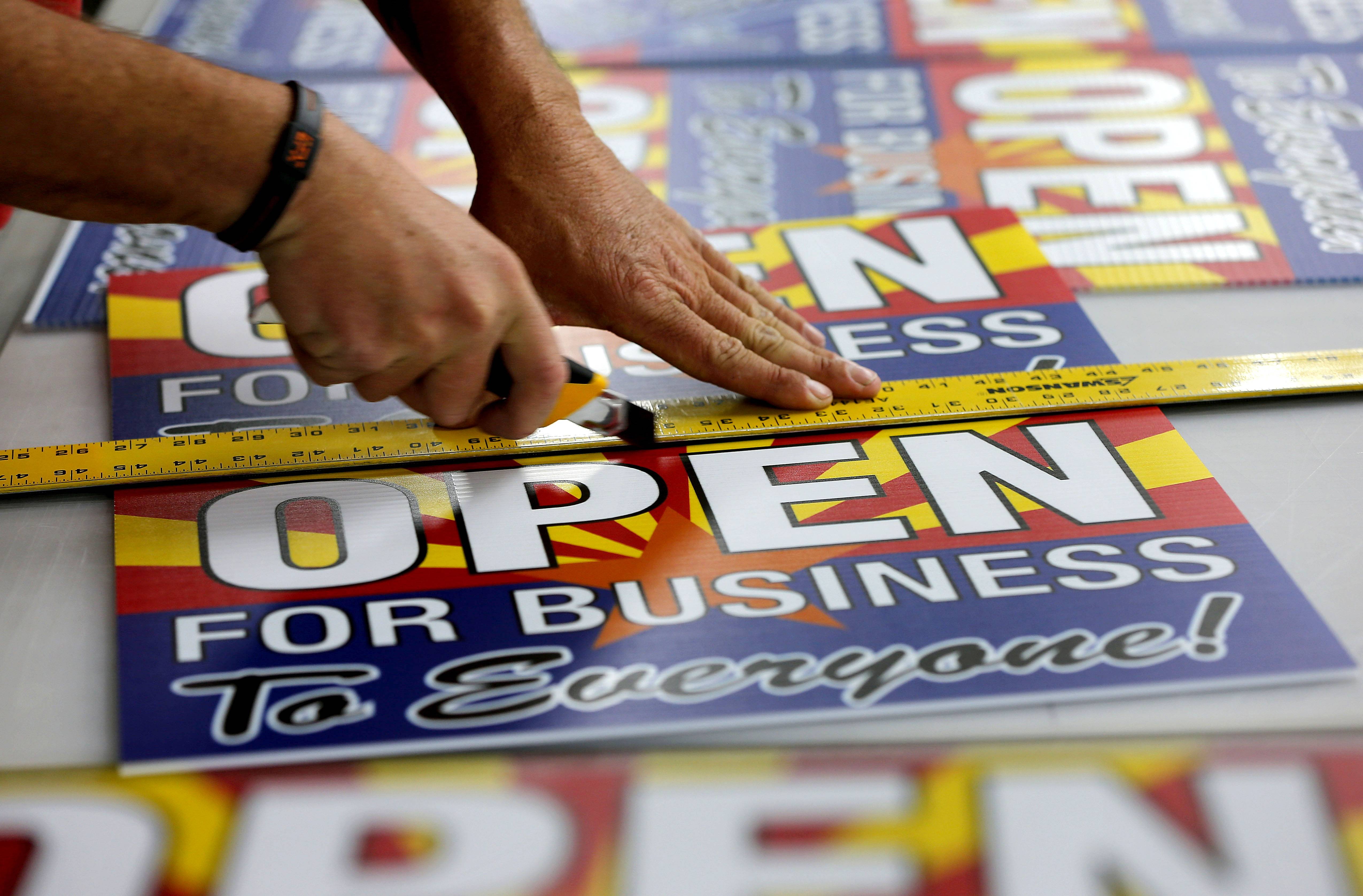 "Tom Cushing, a production expert at Fast Signs, cuts down a sheet of anti-Senate Bill 1062 signs that read ""Open For Business To Everyone."""