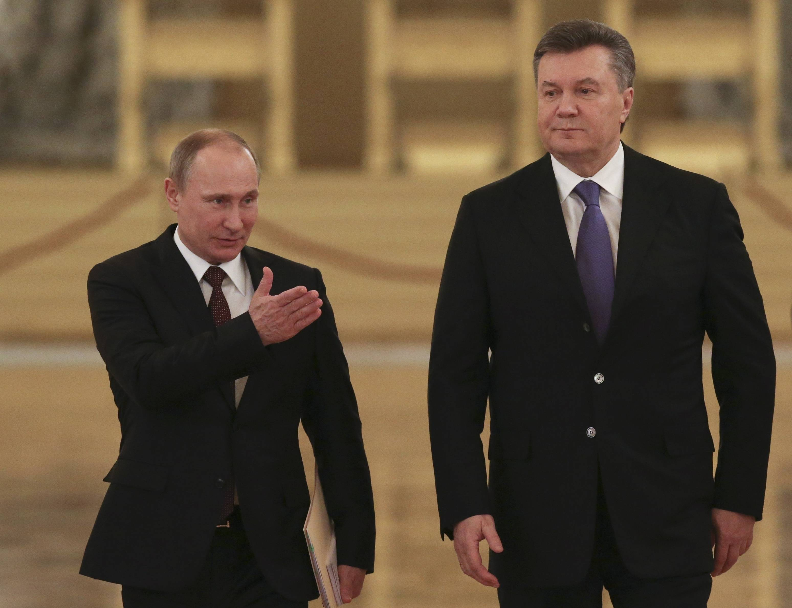 "Russian President Vladimir Putin, left, shows the way to his Ukrainian counterpart Viktor Yanukovych during a meeting in the Kremlin in Moscow, Russia. Moscow on Wednesday granted Ukrainian President Viktor Yanukovych protection ""on the territory of Russia,"" shortly after the fugitive leader sought help from the Kremlin, according to an official quoted by Russian news agencies."