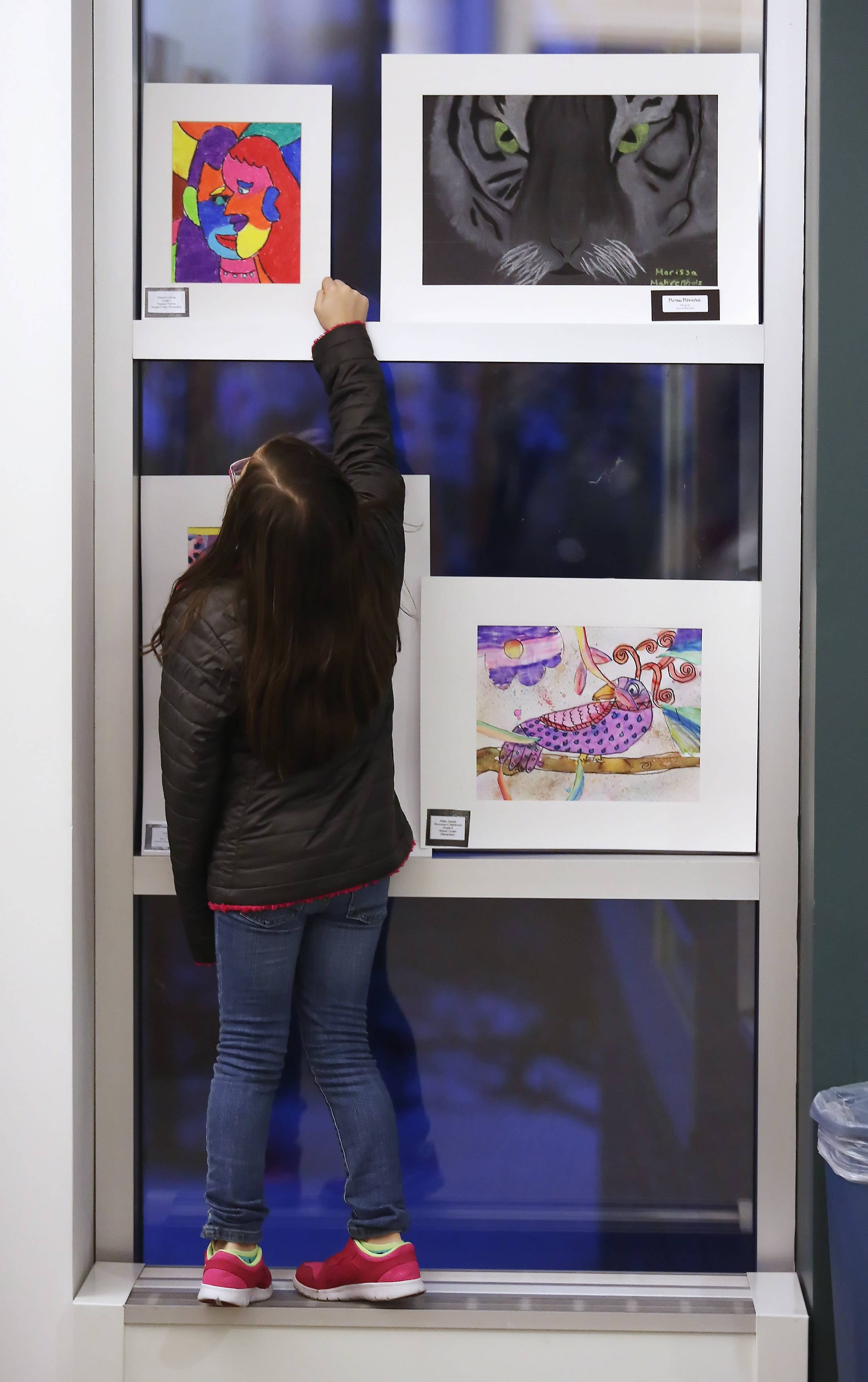 Gilbert R. Boucher II/gboucher@dailyherald.comThird grader Tahiz Hernanadez looks up at a picture by Robert Crown School third grader Delany Lemay during the Studio 118 Art Show Open House by Wauconda School District 118 Thursday at Wauconda Area Library. The show featured over 600 artworks from students in Wauconda.