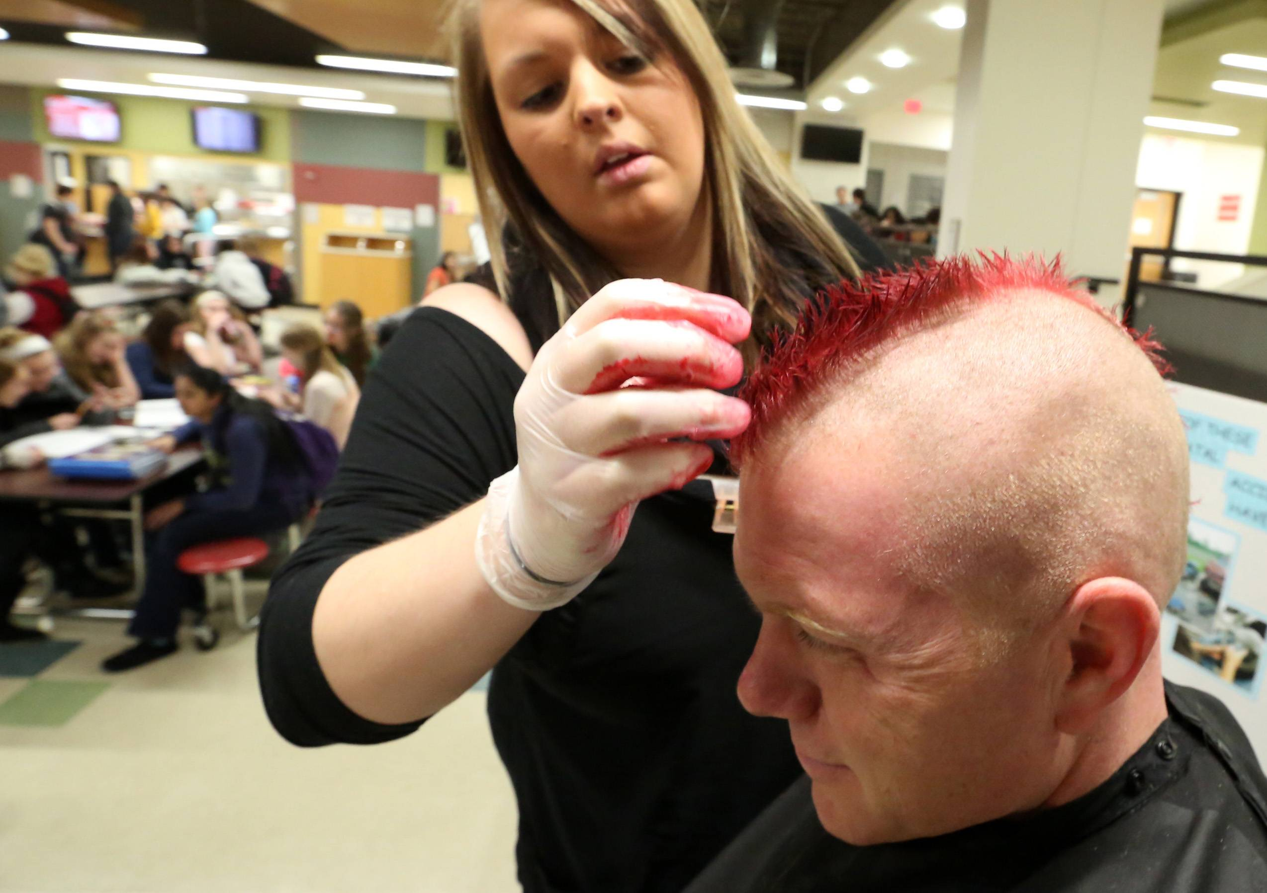 George LeClaire/gleclaire@dailyherald.comGrant Community High School's resource officer Russ Zander has his mohawk haircut died red by Kaitlyn Vinyard, a stylist with Grand Avenue Hair Club, on Friday in the school's lunch area in Fox Lake.