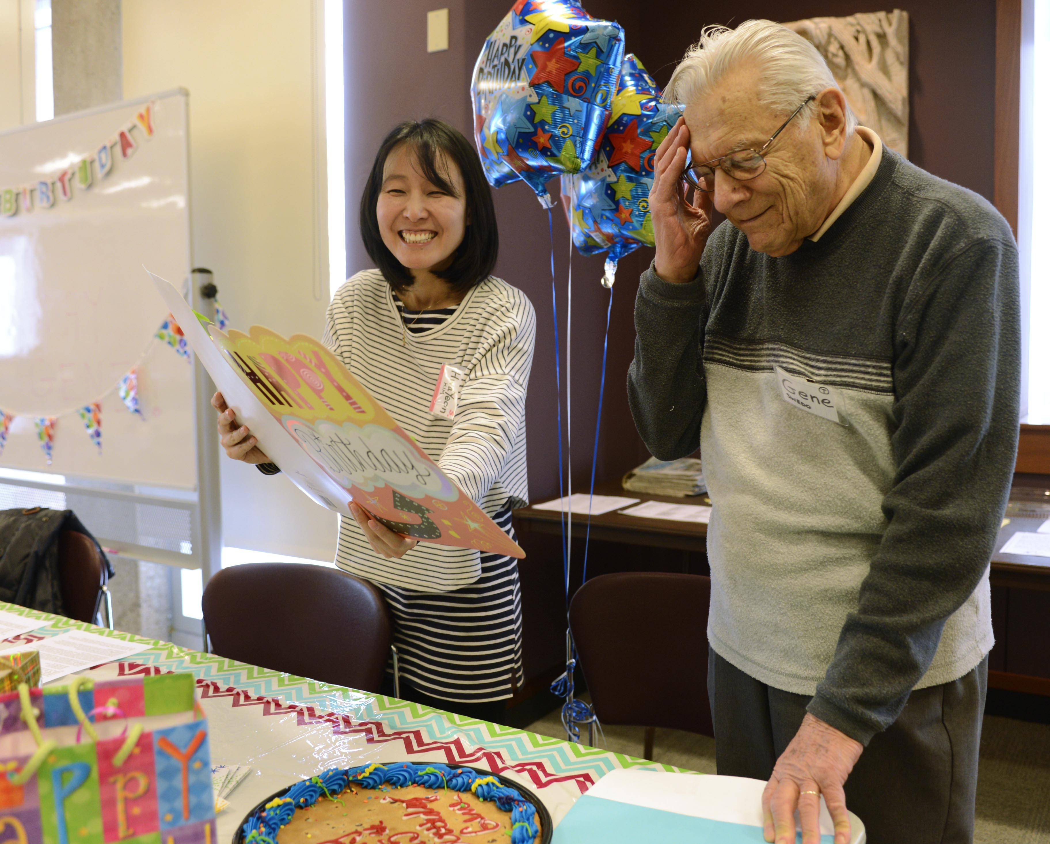Joe Lewnard/jlewnard@dailyherald.comEnglish as a Second Language student Hwa Yeon Kim, of Buffalo Grove, holds a birthday card during a surprise party for 95-year old Mount Prospect volunteer Gene Swedo at the Mount Prospect Public Library Friday.
