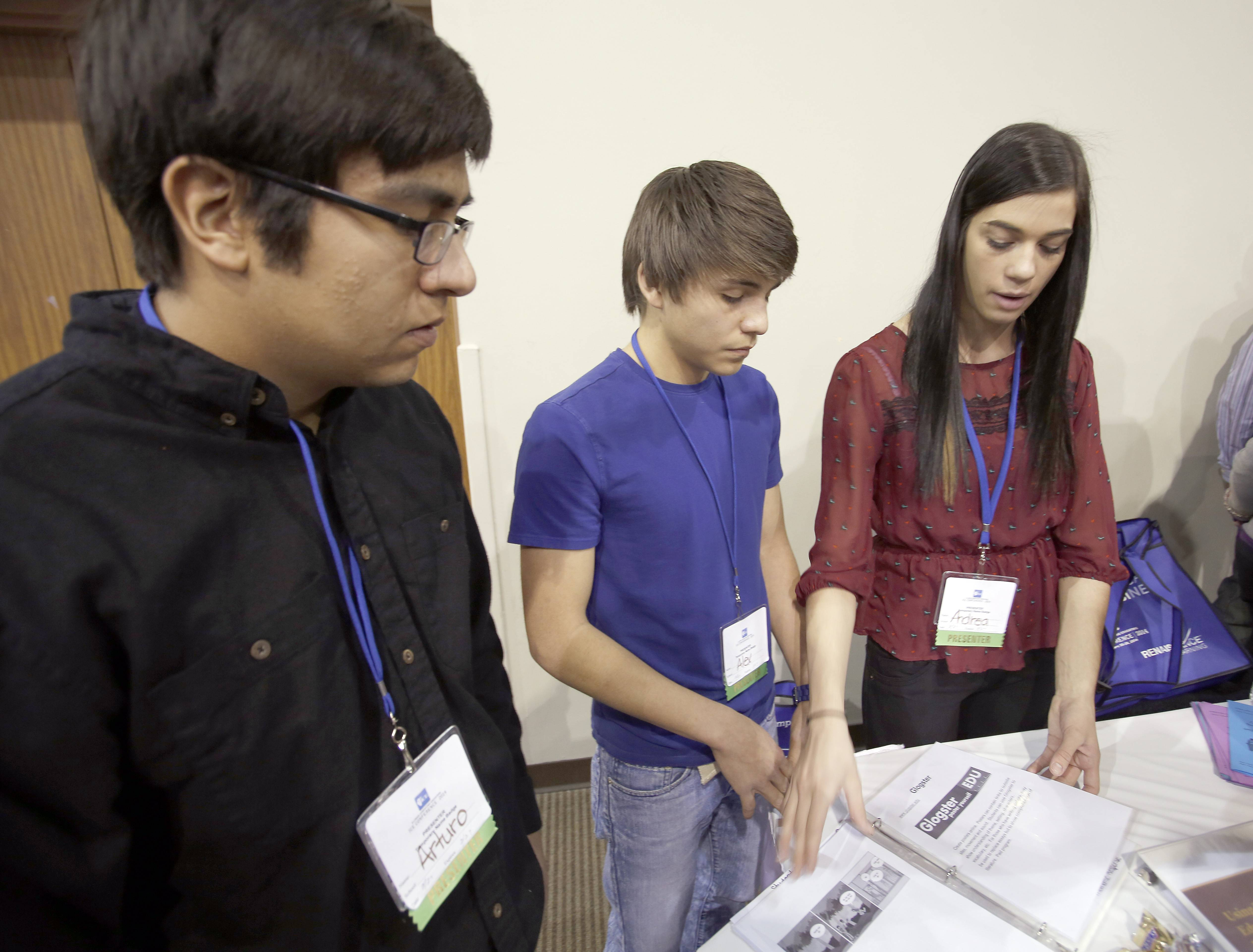 Arturo Silva, 17, from left, Alex Ochoa, 16, and Andrea Petrarca, 18, explain how special education students are using technology at Kaneland High School during the Illinois Computing Educators State Conference Thursday at Pheasant Run in St. Charles.