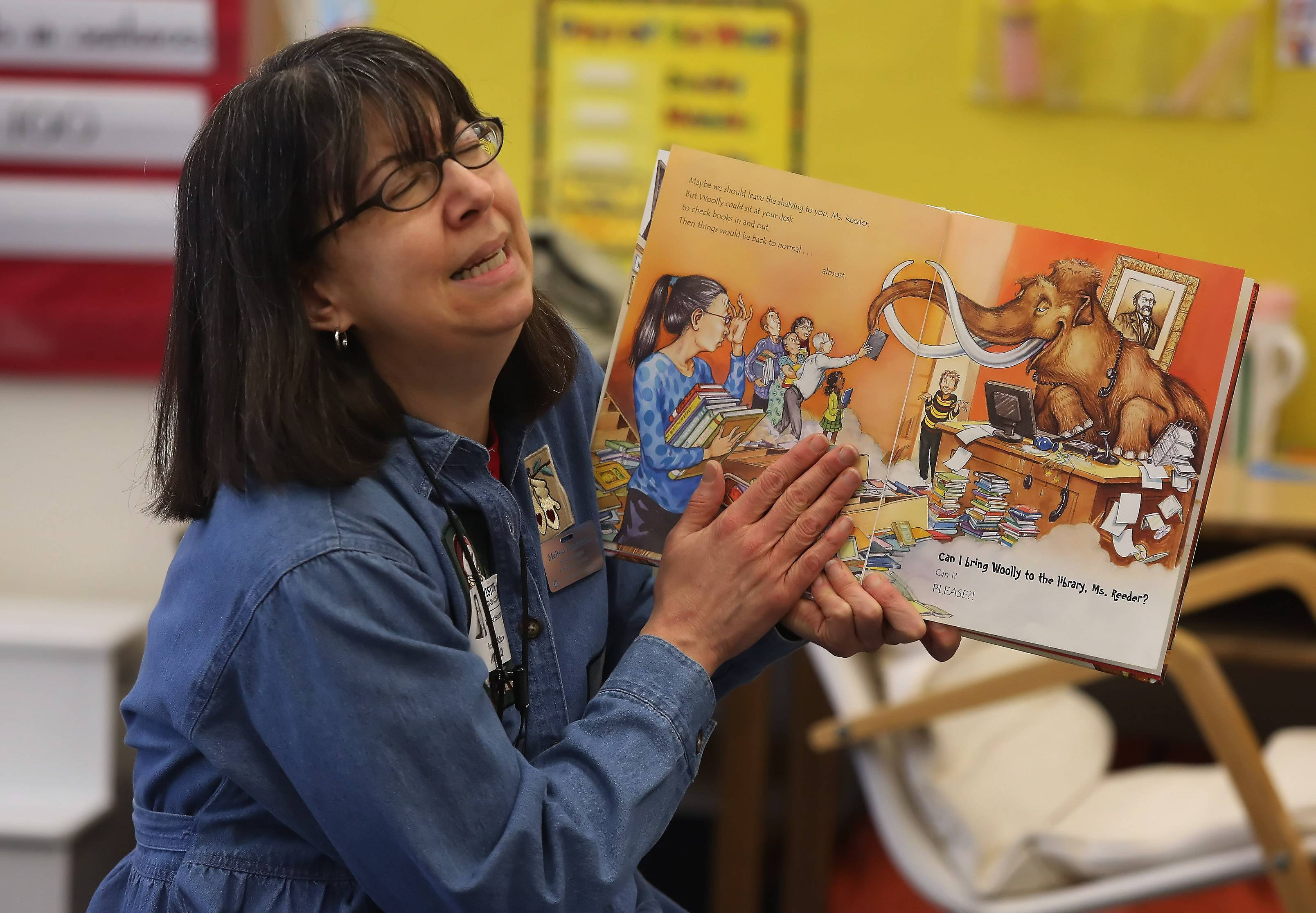 "Cook Memorial Public Library children services librarian Melissa Henderson reads the book ""Can I Bring Woolly to the Library, Ms. Reeder"" by Lois G. Grambling to students during Kindergarten Career Fair Day at Rockland School in Libertyville. Kindergartners learned about jobs from a librarian, a firefighter, a human resources director and a therapy dog handler."
