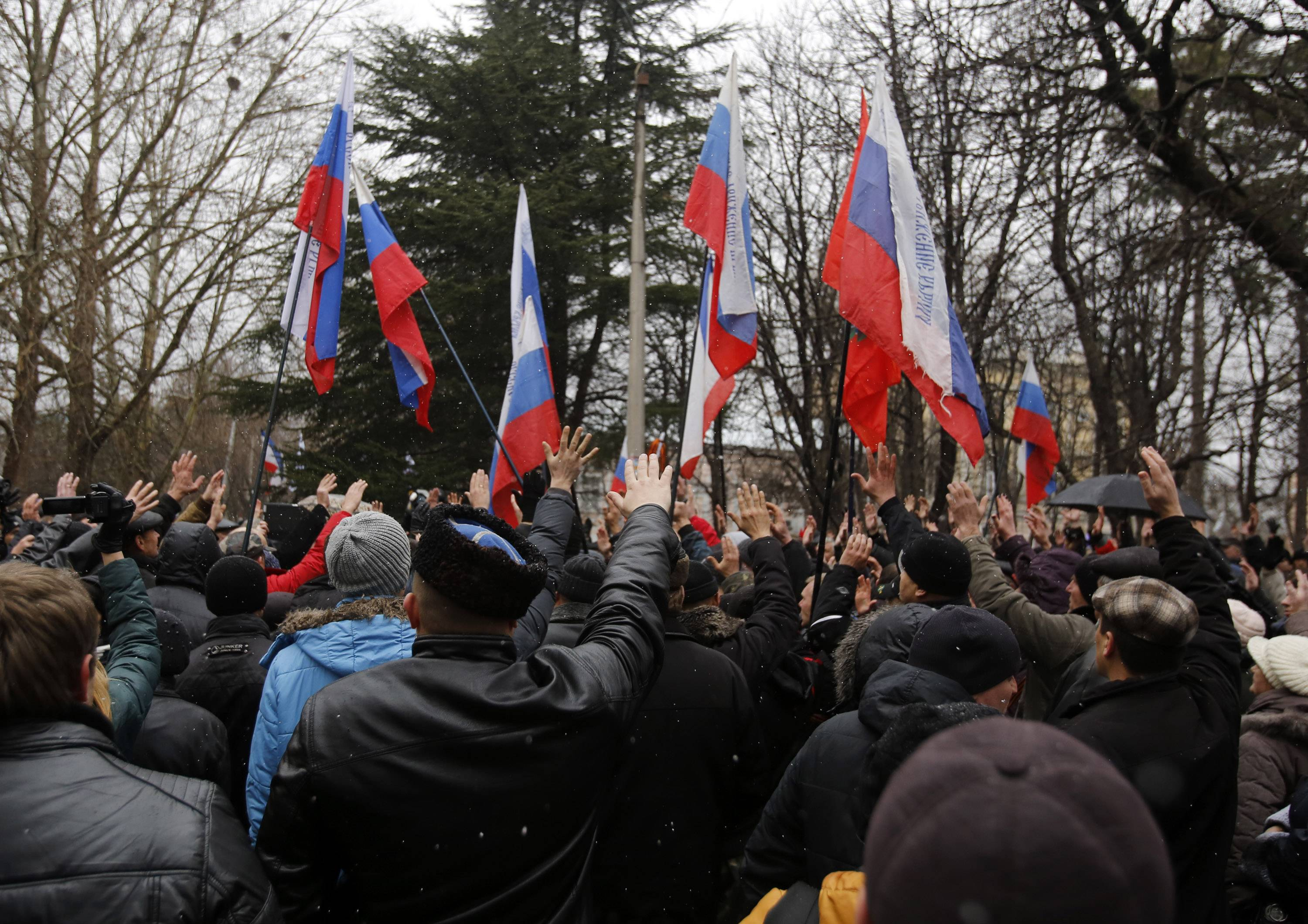 Pro-Russian demonstrators wave Russian and Crimean flags and shout slogans during a protest in front of a local government building in Simferopol, Crimea, Ukraine, Thursday.