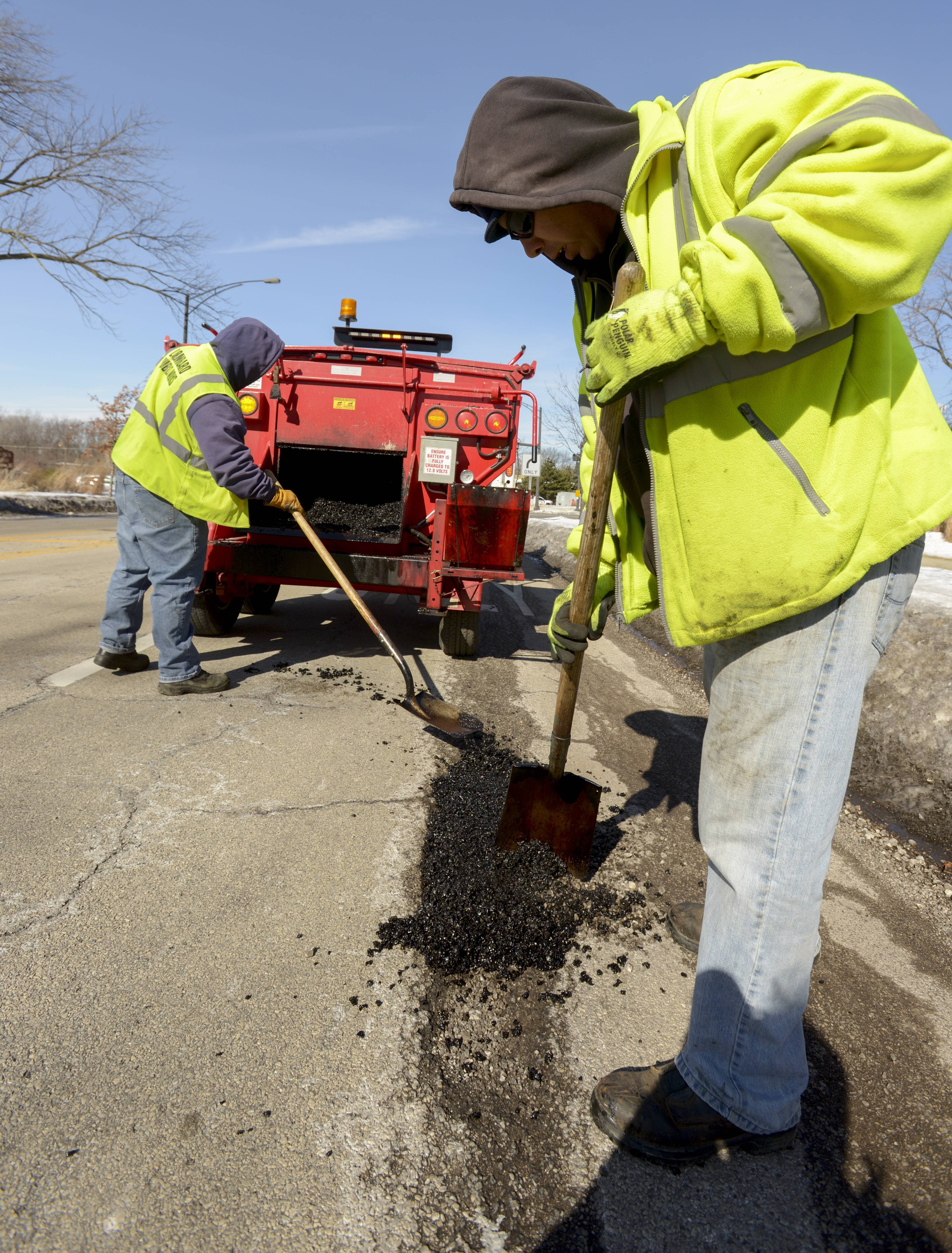 Lombard public works employees fill potholes along Grace Street.