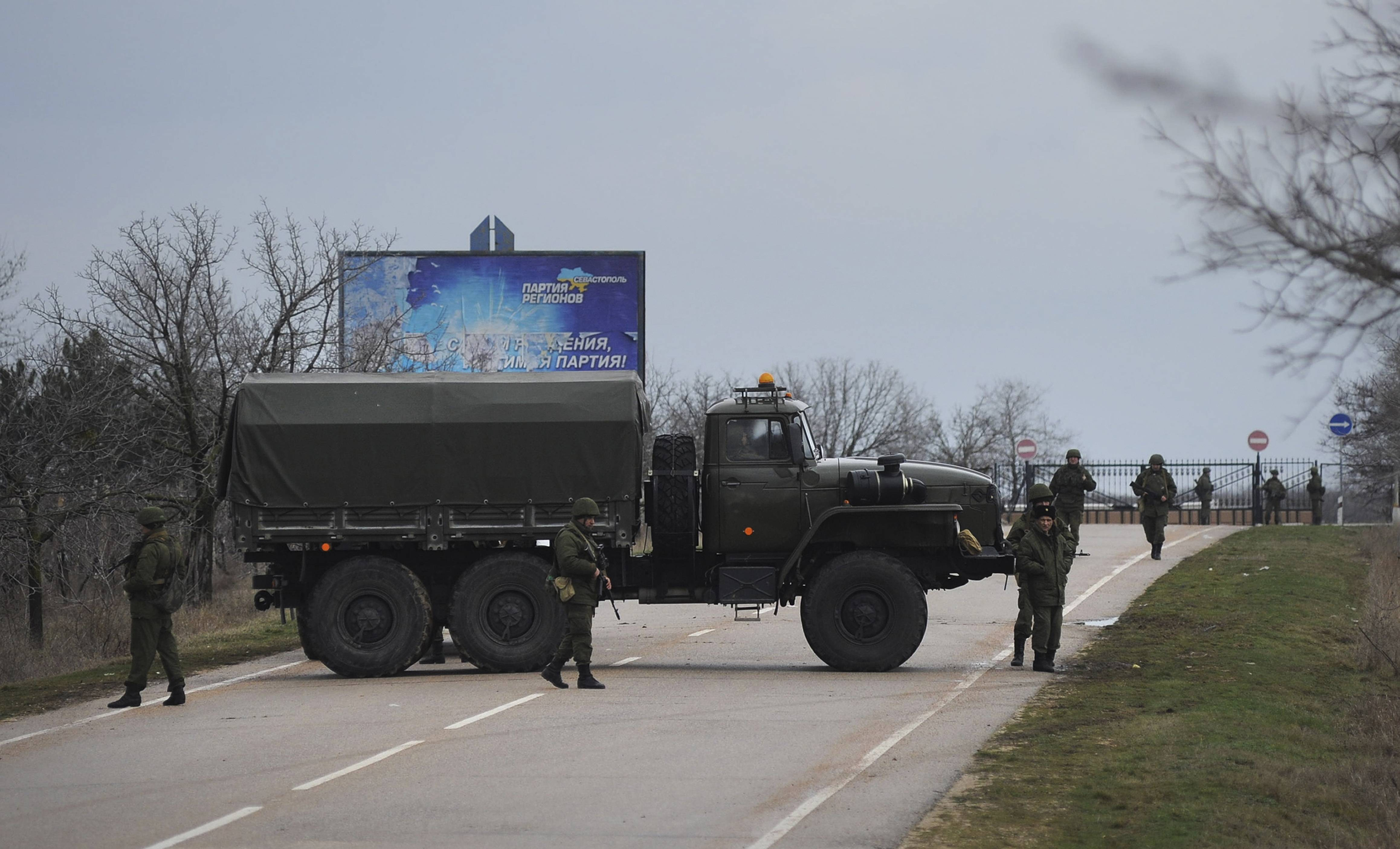 Russian troops Friday block the road toward the military airport at the Black Sea port of Sevastopol in Crimea, Ukraine. Heightened security is evident with Russian military around Sevastopol, the location for Russia military bases, military airport and Naval Base, while unidentified armed men wearing uniforms without insignia were patrolling another airport serving the regional capital, Ukraine's new Interior Minister Arsen Avakov said on Friday.