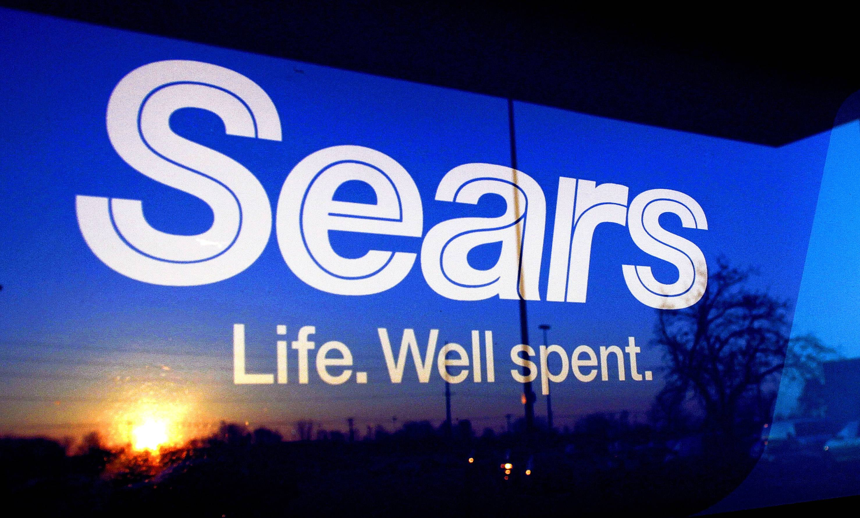 The setting sun is reflected on a window with the Sears logo, in Springfield, Ill. Sears may have suffered a cyber attack that breached the company's data systems.