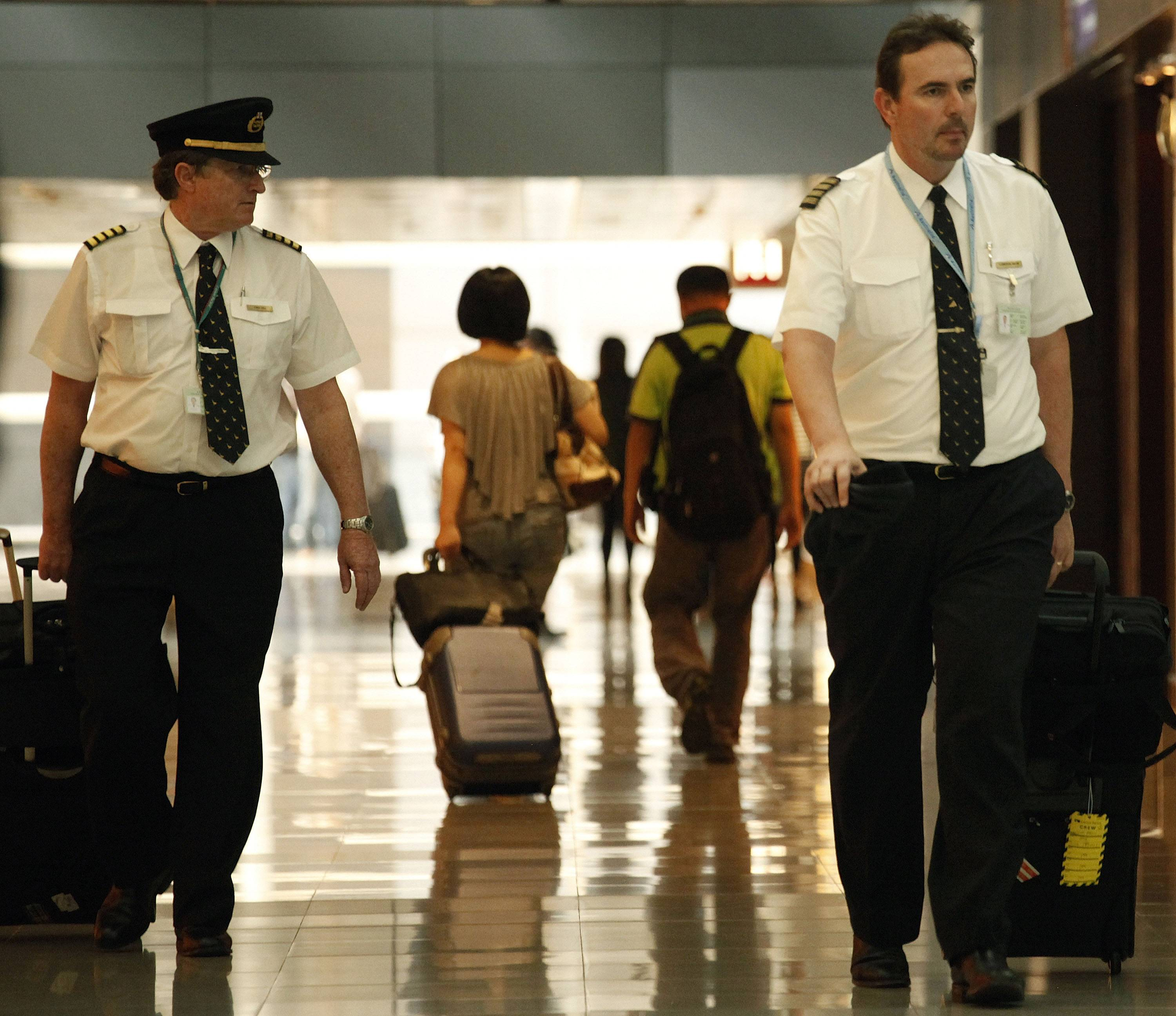 In this  Nov. 30, 2011 photo, two pilots from Cathay Pacific walk in the Hong Kong International Airport in Hong Kong.  The U.S. airline industry will need to hire 1,900 to 4,500 new pilots annually over the next 10 years due to an expected surge in retirements of pilots reaching age 65 and increased demand for air travel, the Government Accountability Office said in the report obtained late Thursday, Feb. 27, 2014.