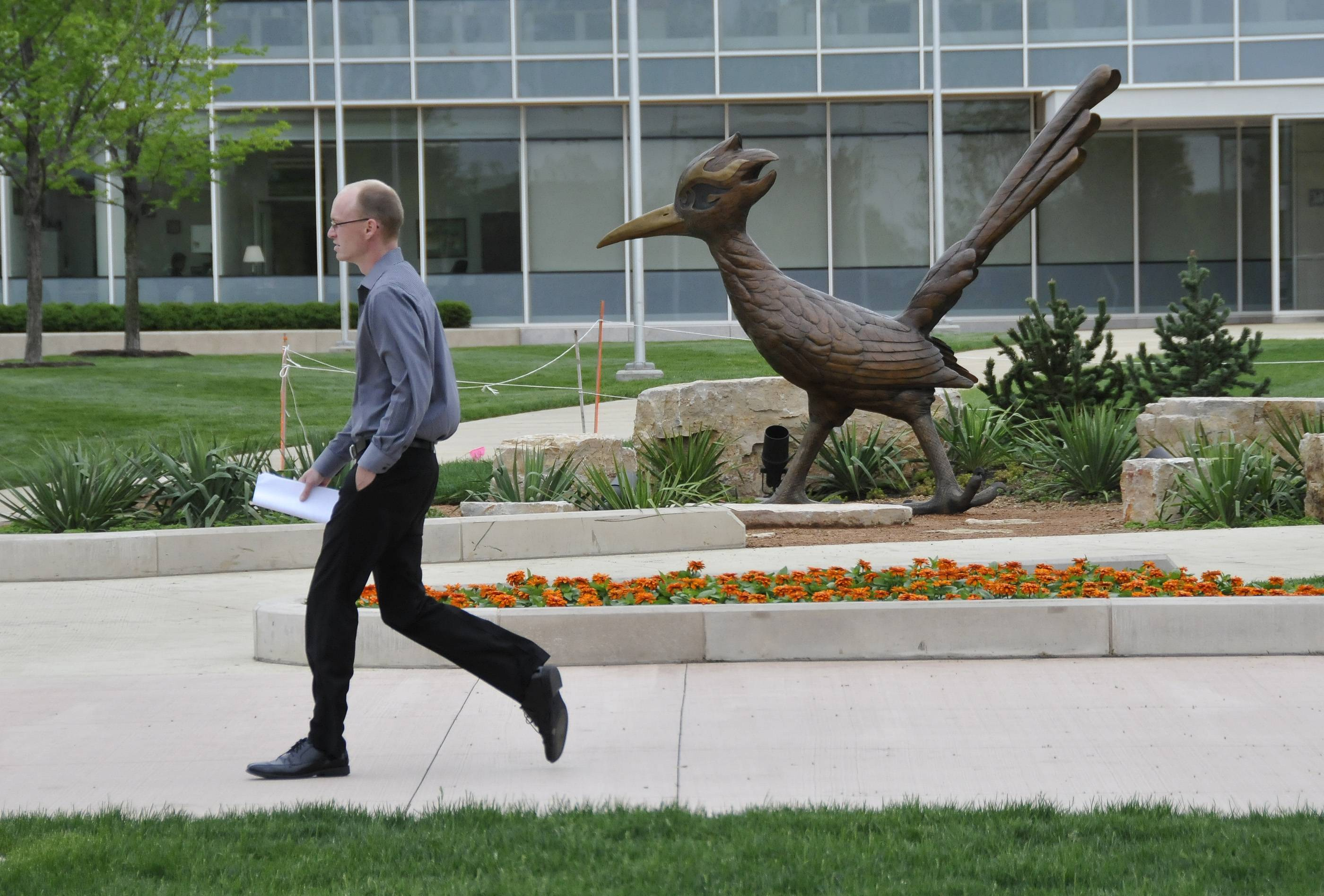A man passes by a sculpture of a chaparral on the campus of College of DuPage. Travel reimbursements to COD trustees are raising eyebrows.