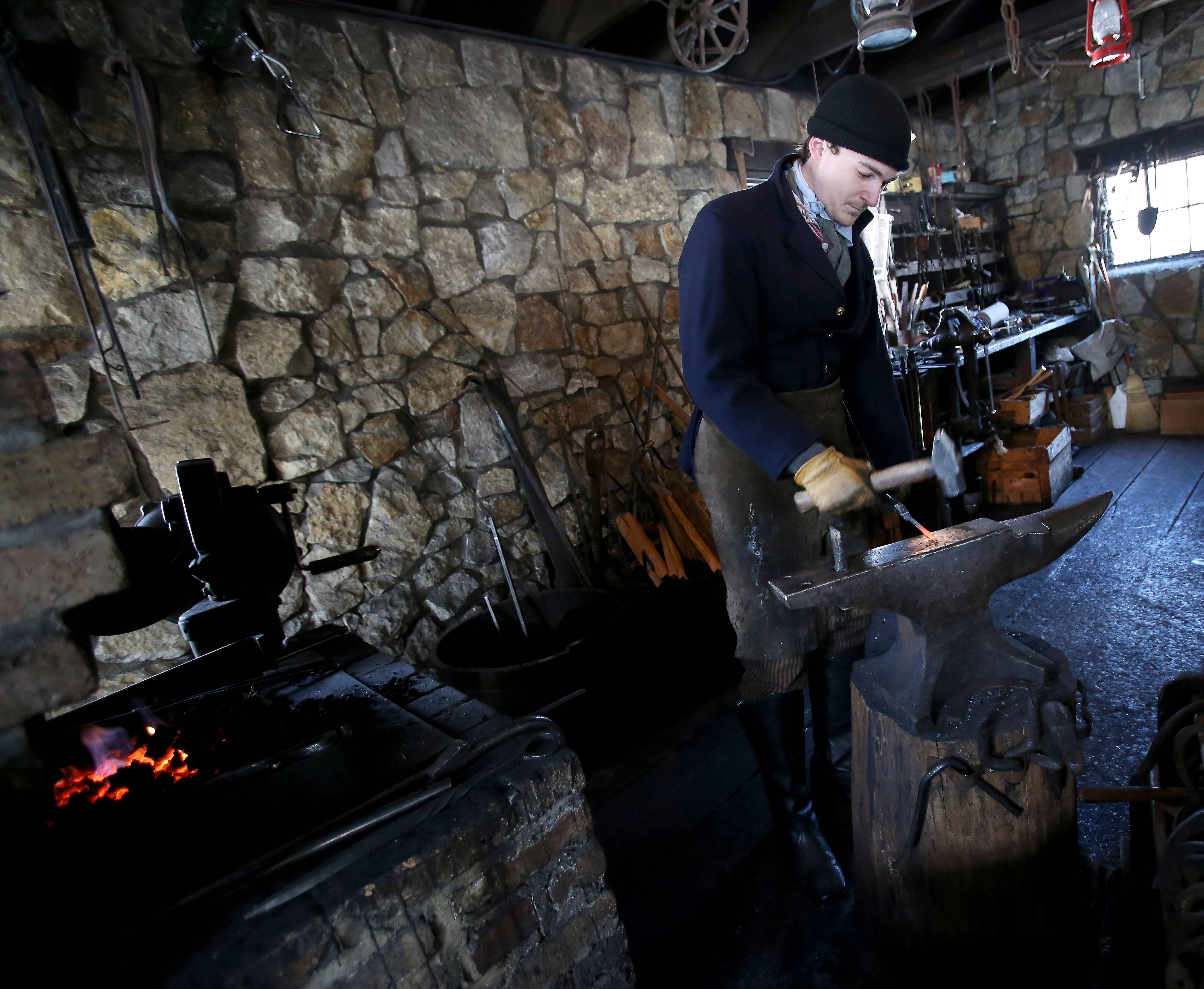 Justin Stech, a museum educator at Naperville's Naper Settlement, demonstrates his blacksmithing skills Friday for kids participating in the Fire and Ice School's Out program.