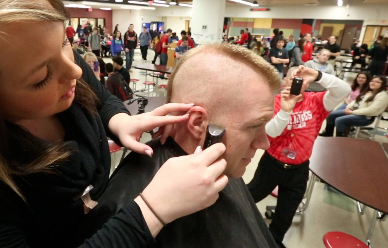 Grant Community High School students watch Friday as resource officer Russ Zander has his head shaved into a mohawk cut by Kaitlyn Vinyard, a stylist with Grand Avenue Hair Club in the Fox Lake school's lunch area.