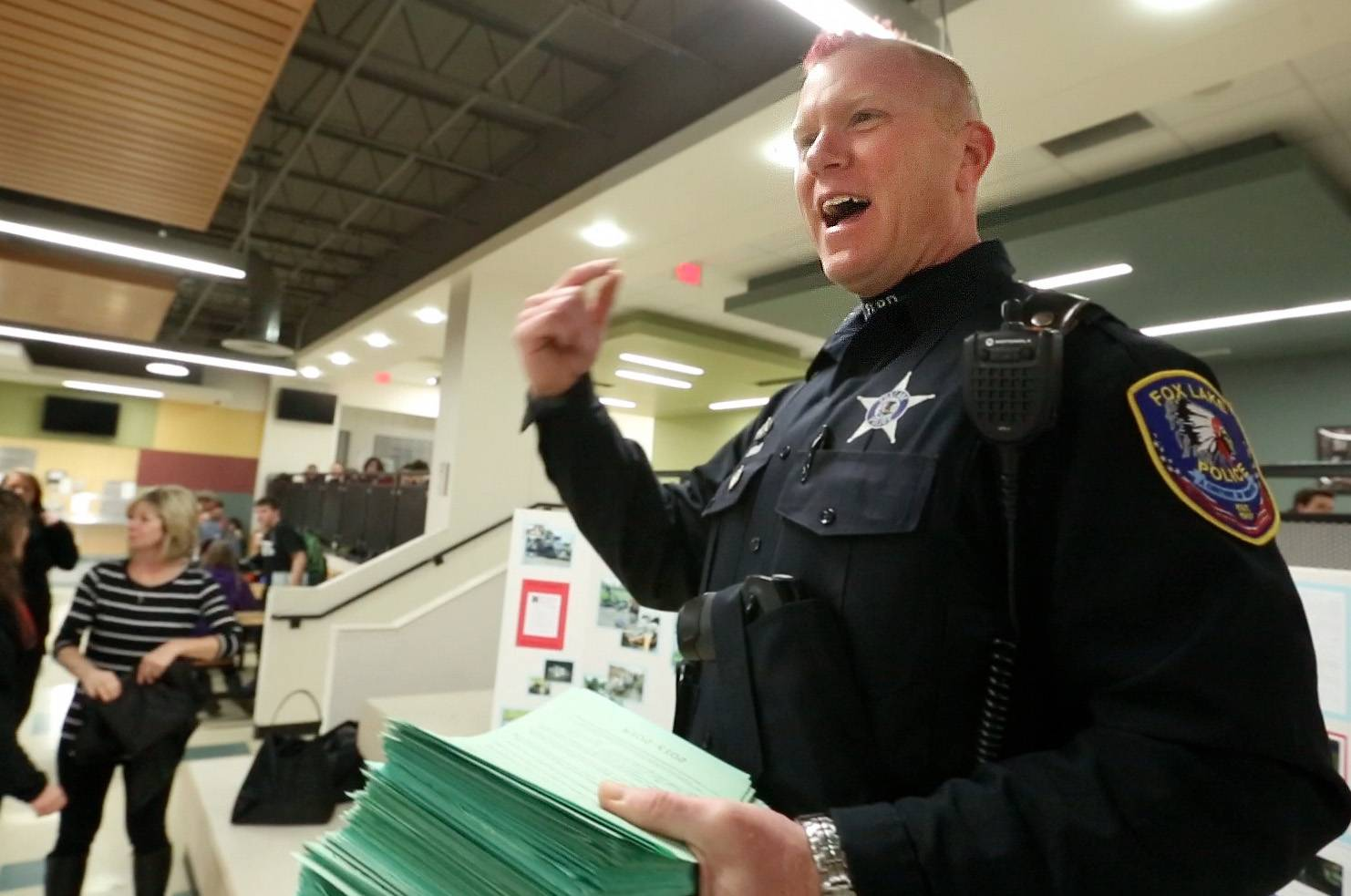 Grant Community High School resource officer Russ Zander tells students he got a red mohawk hair cut because more than 850 of them signed pledges not to text while driving.