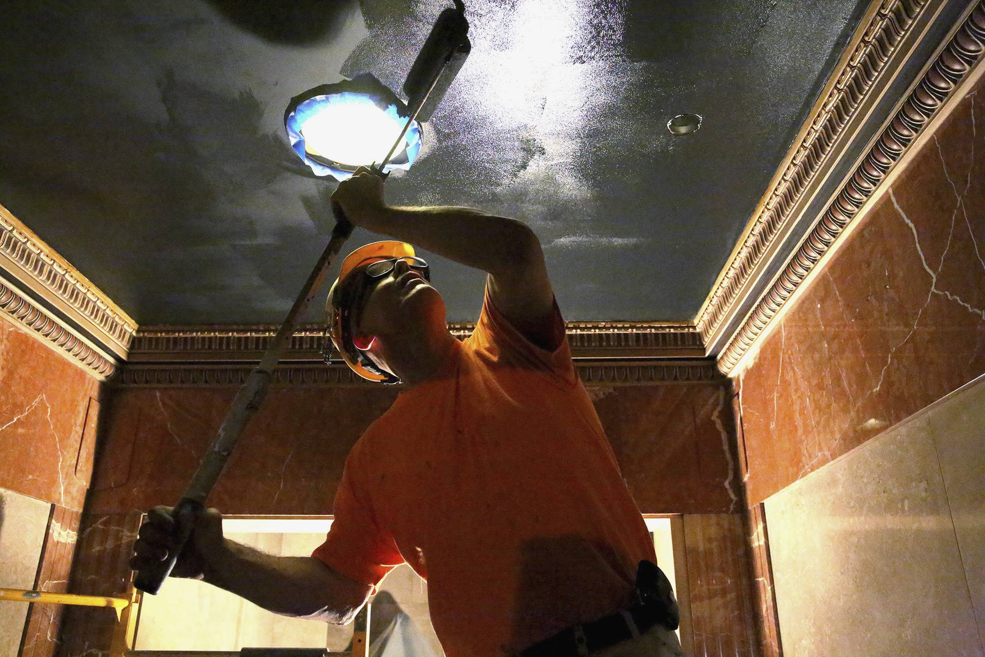 David Giese applies black paint to the ceiling of a hallway at the Abraham Lincoln tomb in the Oak Ridge Cemetery in Springfield.