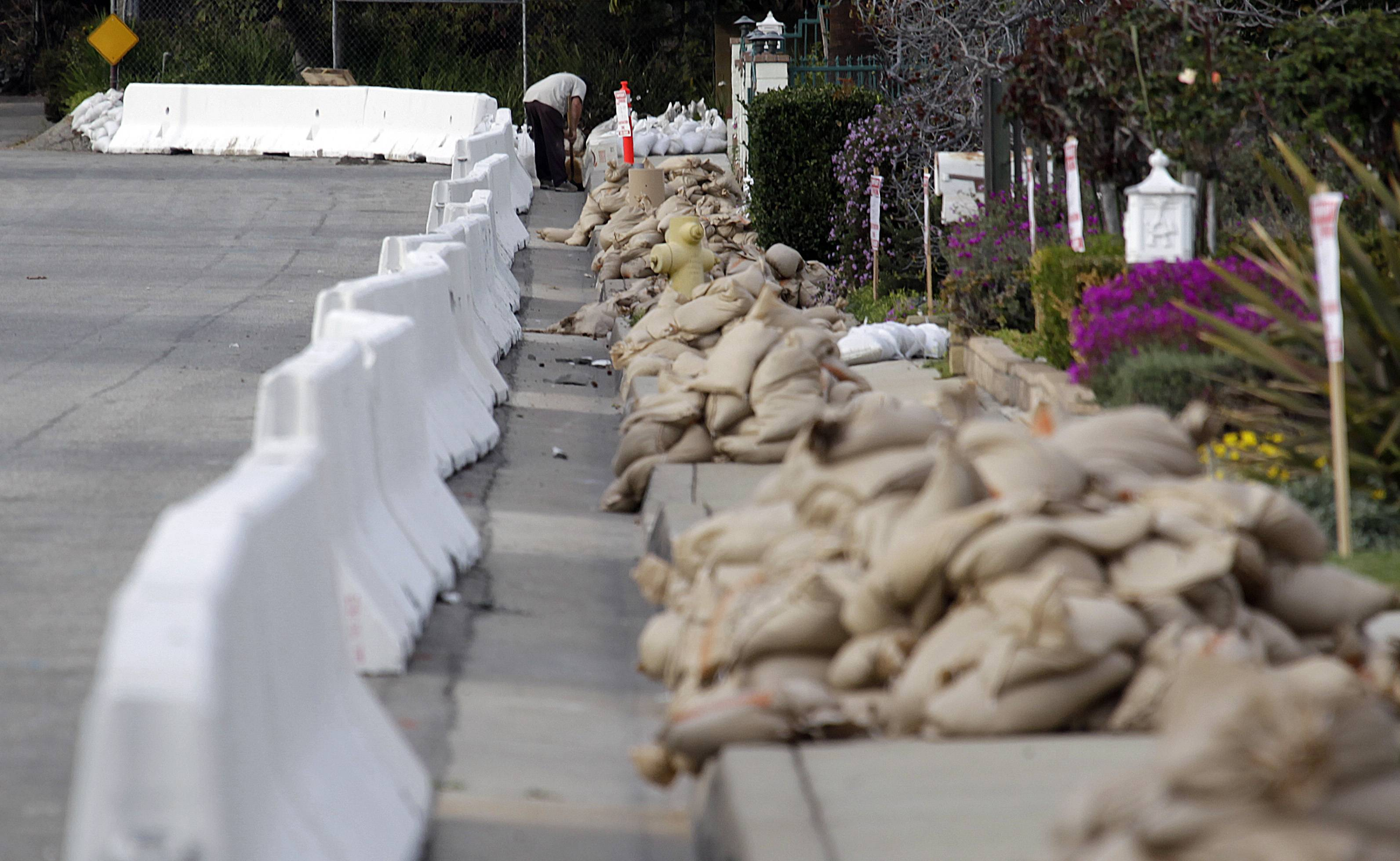 A man Thursday places sandbags at the top of a street lined with K-rail and sandbags in Glendora, Calif., as the city and residents prepare for possible flooding. Mandatory evacuation orders have been issued for 1,000 homes in two foothill suburbs east of Los Angeles in advance of a powerful storm. The cities of Glendora and Azusa issued the orders at midday Thursday for homes that could be endangered by debris flows from nearly 2,000 acres of steep mountain slopes burned by a wildfire last month. For days, both cities have been making extensive preparations including sandbagging. California received widespread rain Wednesday and early Thursday from the first of two back-to-back storms. The more powerful second storm is due overnight.