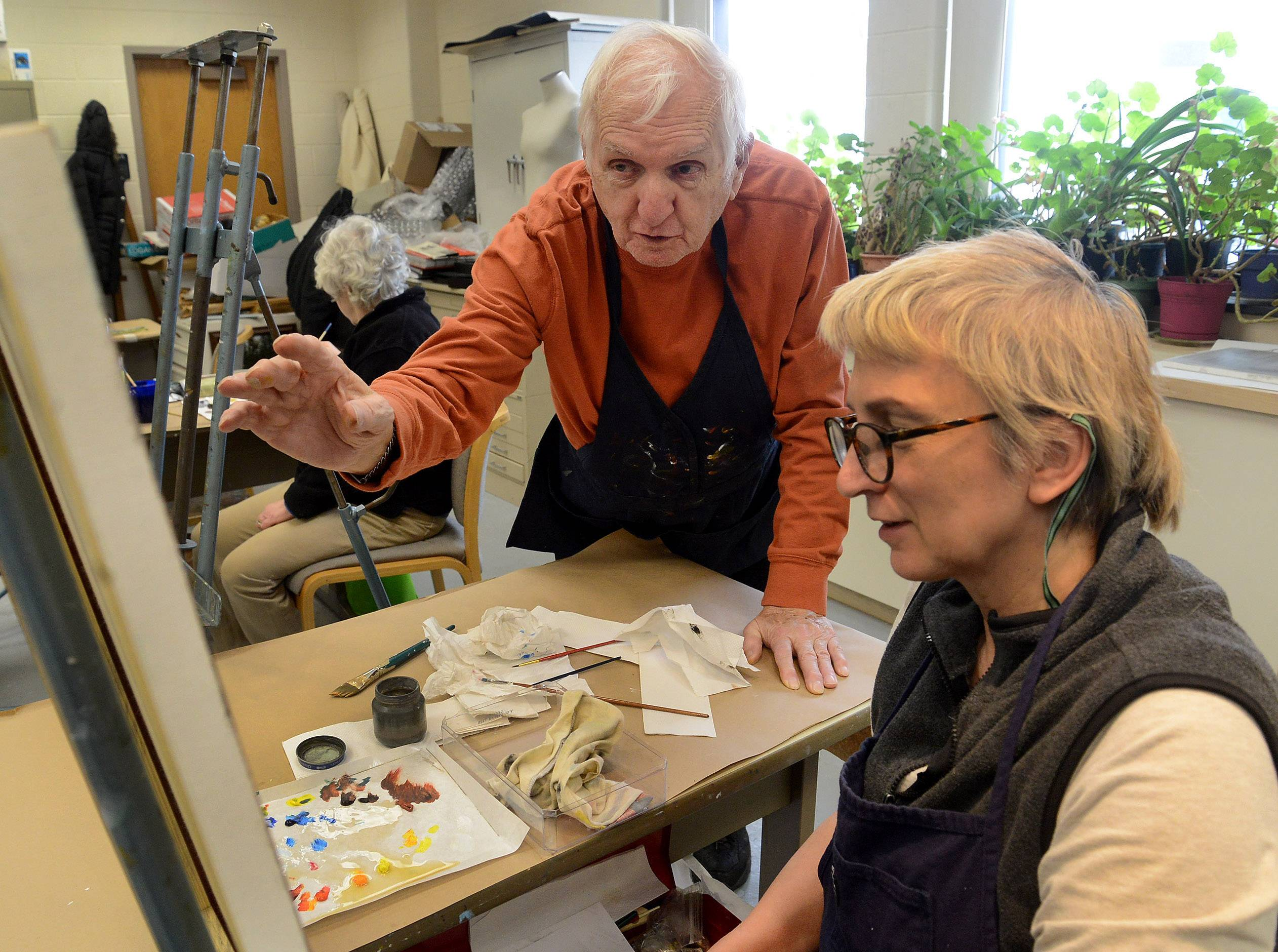 Chuck McCann gives some advice to fellow student Marilyn Pearson of Antioch during an art class at College of Lake County.