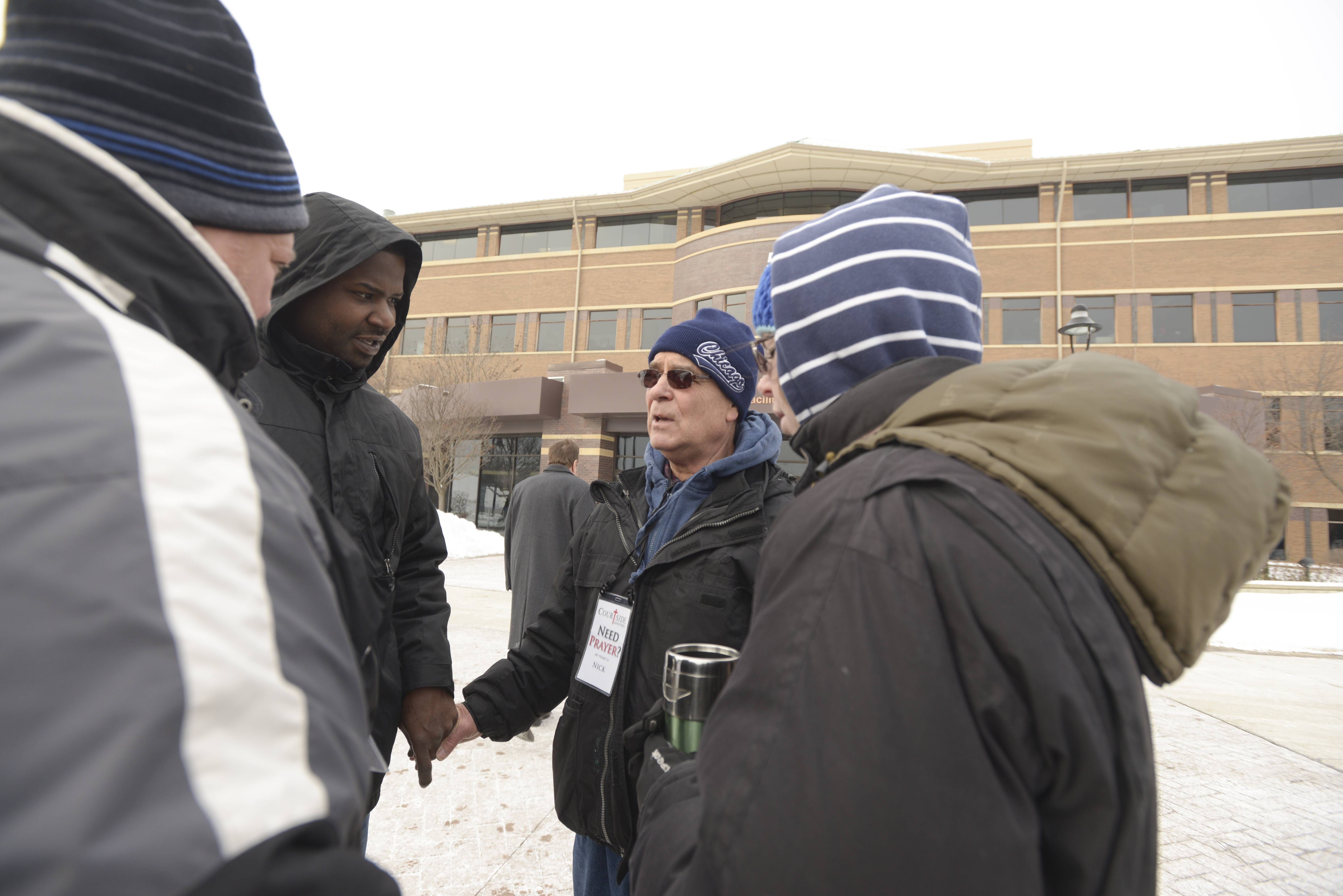 Members of Courtside Ministries offer prayer to Steven Garner of Bartlett, center left, outside the DuPage County courthouse. The volunteers are, from left, Ken Schrock, Nick Popescu and Kate Perkins.