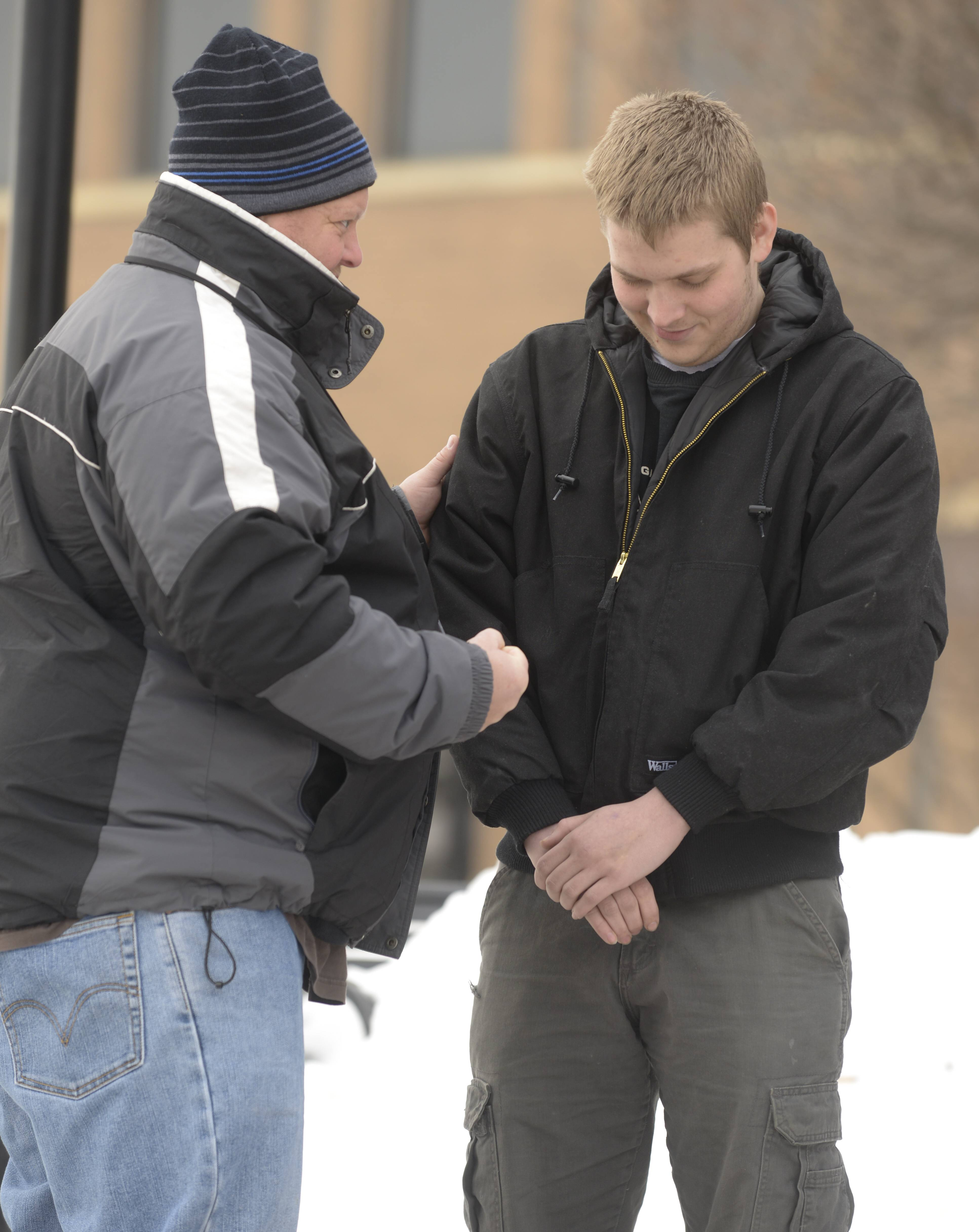 Courtside Ministries DuPage volunteer Ken Schrock prays with Ethan Hartwell, of Elgin, outside the DuPage County courthouse.