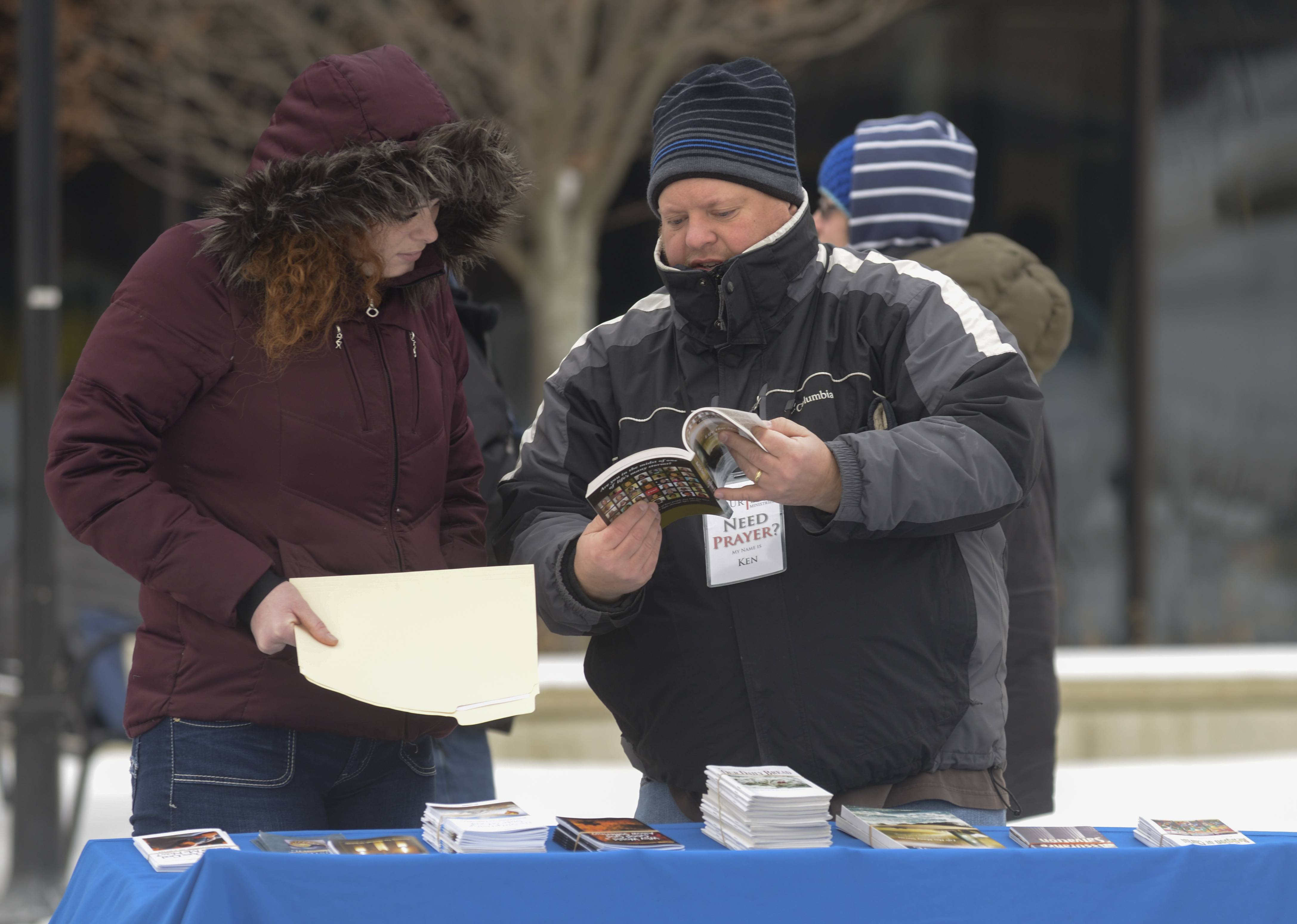 Sara Merritt of Naperville looks over some of the reading material with Courtside Ministries volunteer Ken Schrock of Addison, outside the DuPage County courthouse.