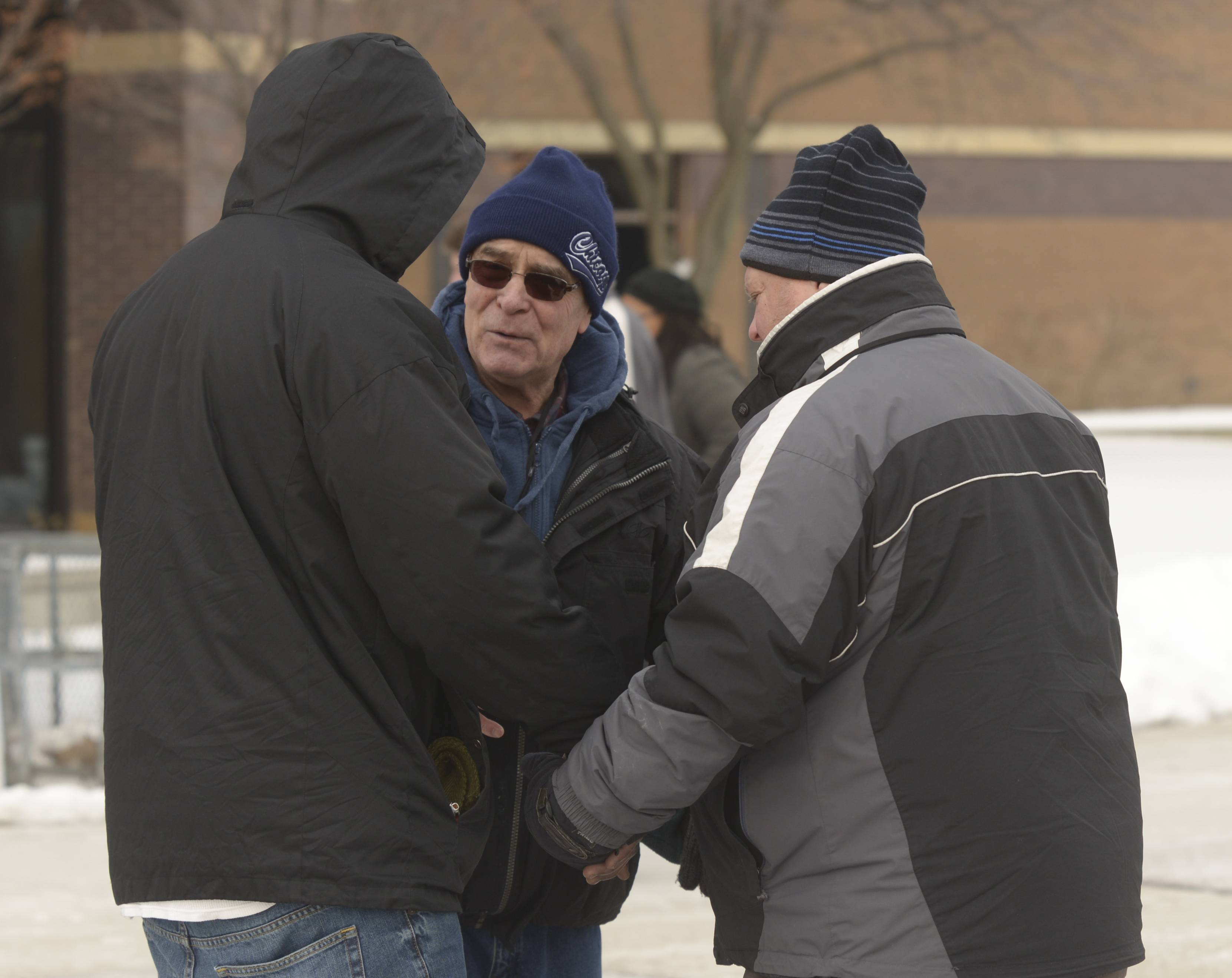 Steven Garner, of Bartlett, prays with Courtside Ministries DuPage volunteers Nick Popescu of Winfield and Ken Schrock of Addison outside the DuPage County courthouse.