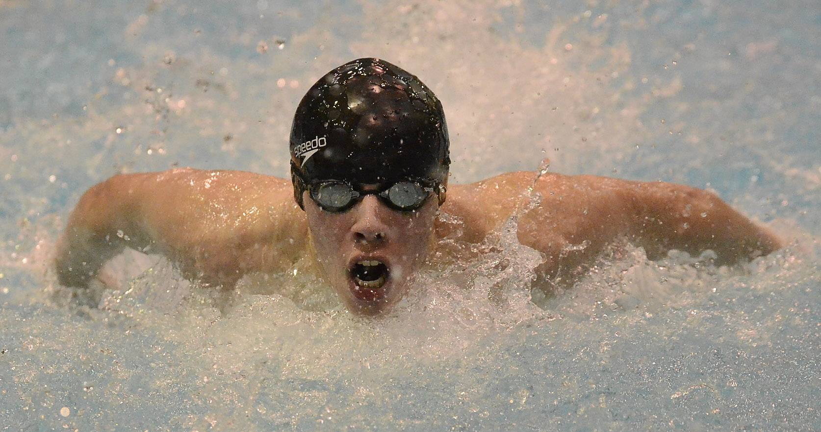 Colin Williams of Elk Grove qualifies 12th in the 100 butterfly during the boys swimming state meet prelims Friday at Evanston Township High School.