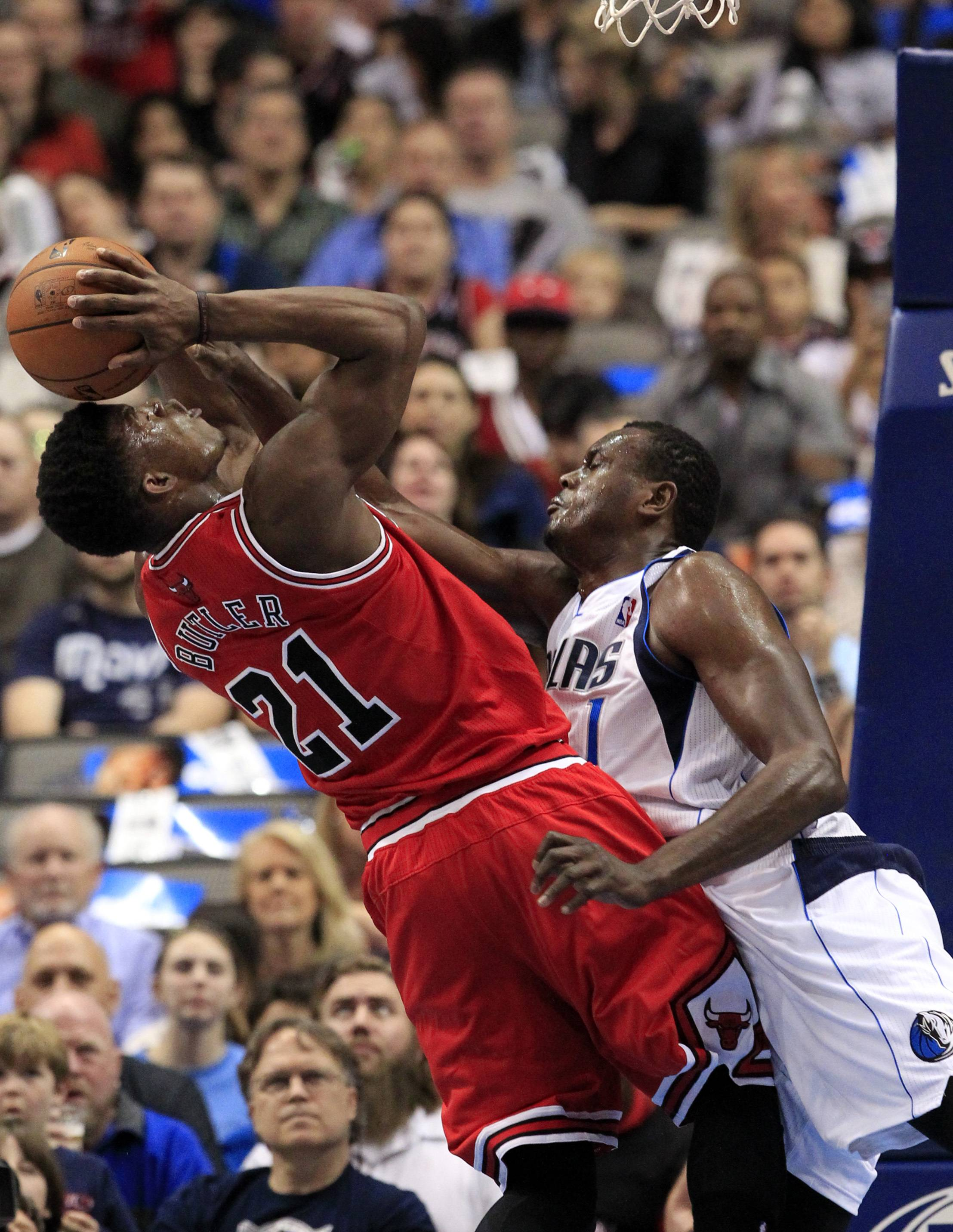 Chicago Bulls guard Jimmy Butler (21) is fouled by Dallas Mavericks center Samuel Dalembert (1), of Haiti, during the first half of an NBA basketball game on Friday, Feb. 28, 2014, in Dallas.
