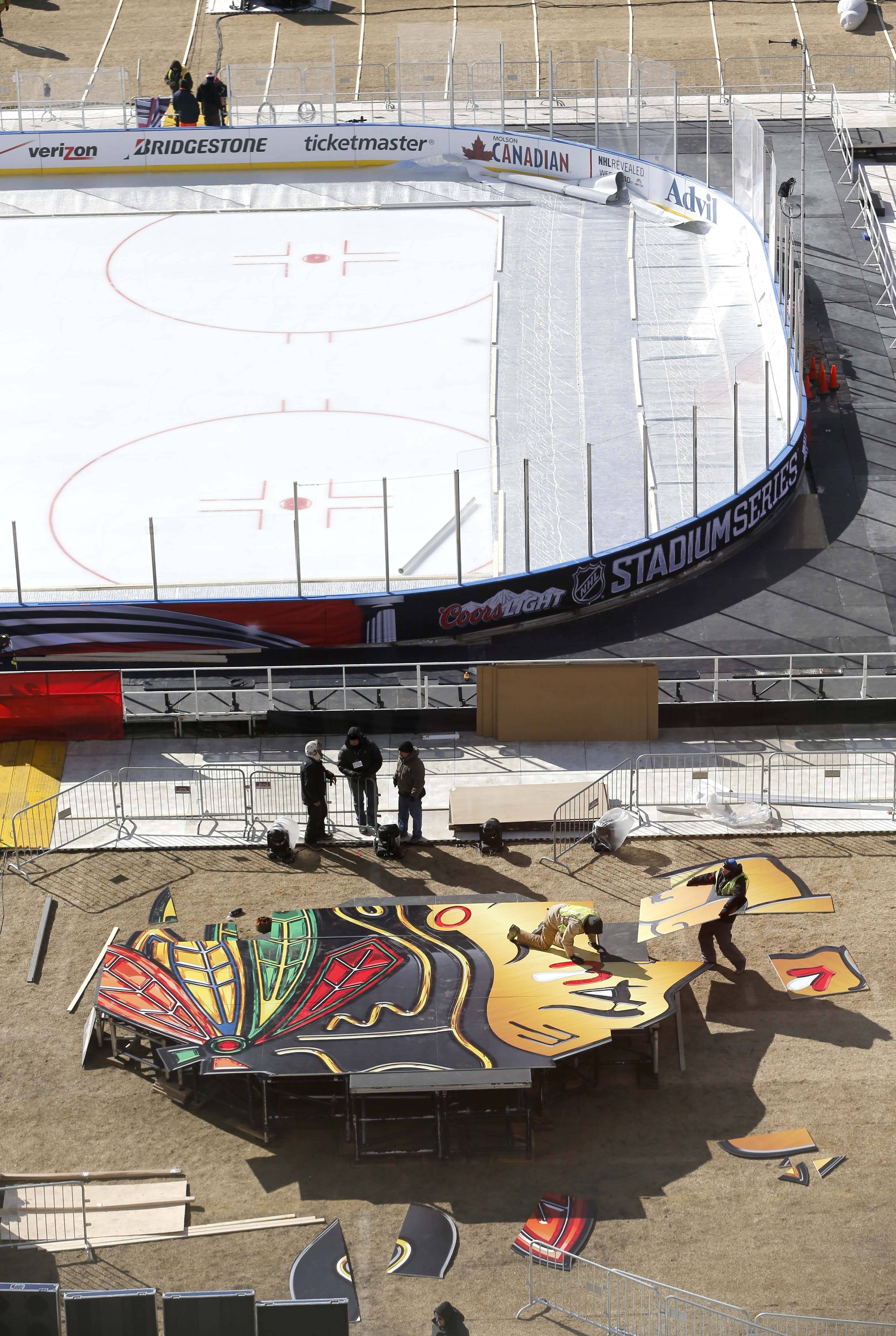 Workers construct a large Blackhawks logo Thursday as they continue to transform Soldier Field for Saturday's Stadium Series NHL hockey game between the Blackhawks and the Pittsburgh Penguins.