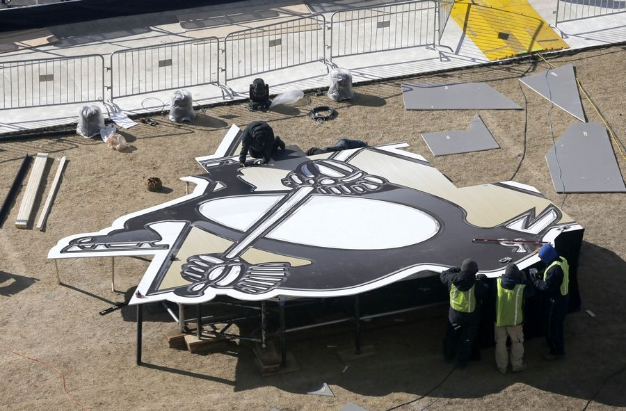 Workers construct a large Pittsburgh Penguins logo Thursday as they continue to transform Soldier Field for Saturday's Stadium Series NHL hockey game between the Blackhawks and the Penguins.