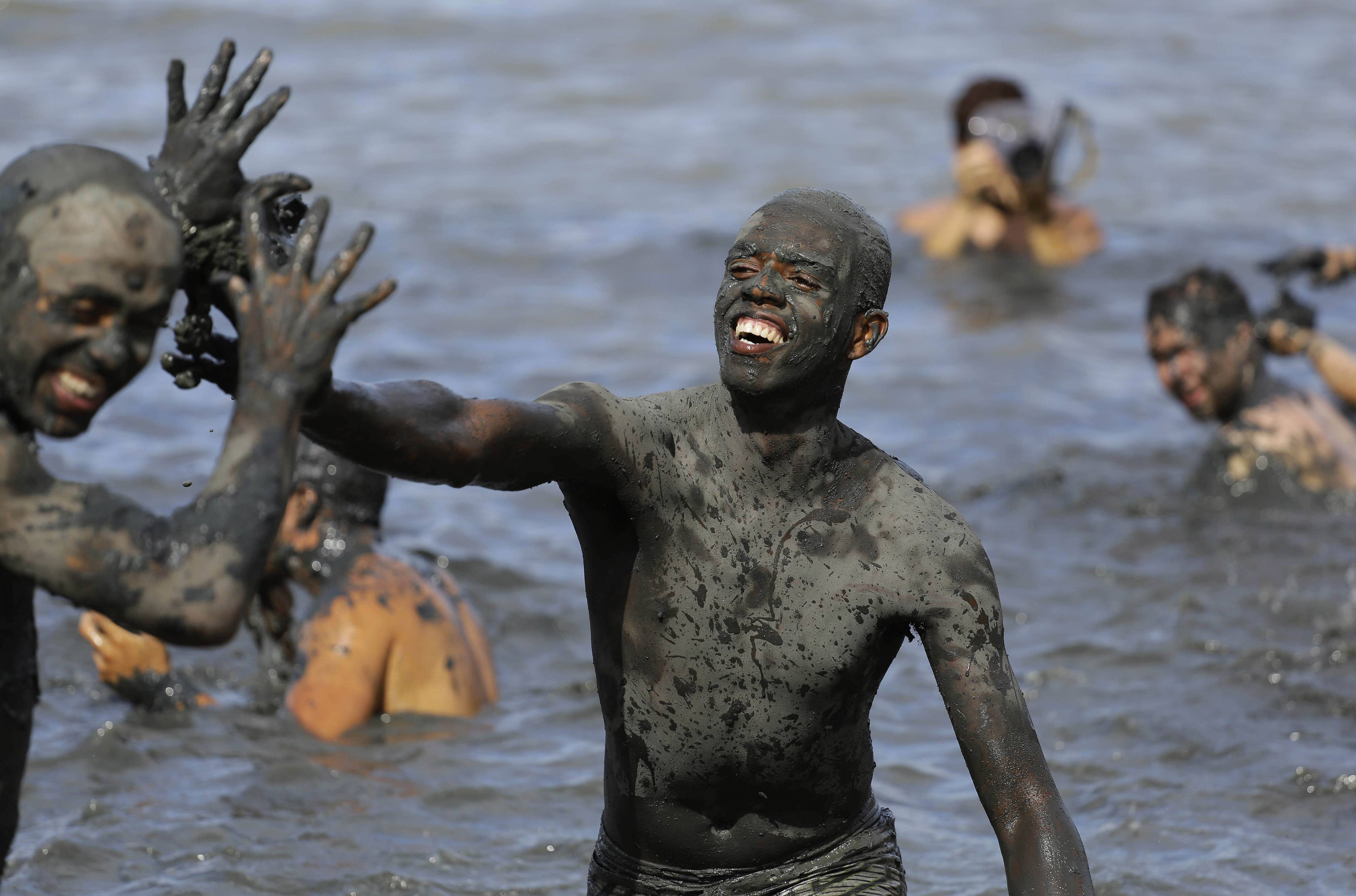 "Mud-covered revelers frolic in ocean waters Saturday during the ""Bloco da Lama"" or ""mud street party"" in Paraty, Brazil."