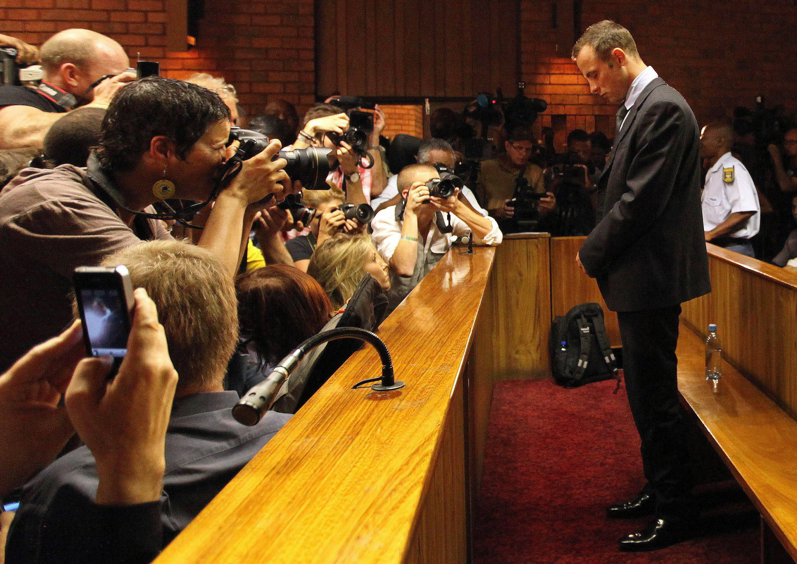 Olympic athlete Oscar Pistorius stands inside a court during his bail hearing in February 2013 at the magistrate court in Pretoria, South Africa. Pistorius will defend himself Monday against a charge of premeditated murder in the slaying of his girlfriend Reeva Steenkamp.