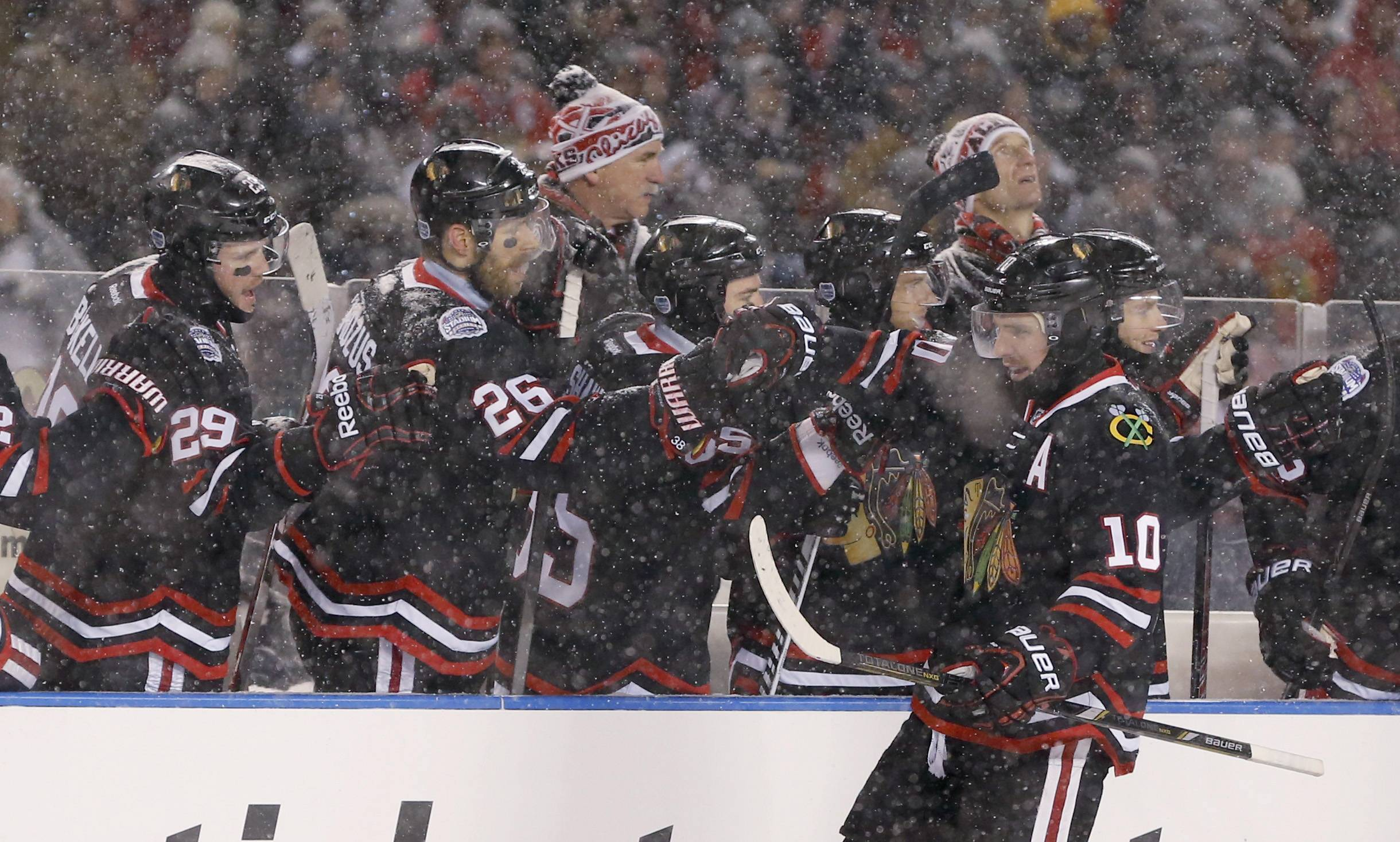 Chicago Blackhawks left wing Patrick Sharp (10) celebrates his goal with teammates on the bench during the first period of an NHL Stadium Series hockey game against the Pittsburgh Penguins at Soldier Field on Saturday.