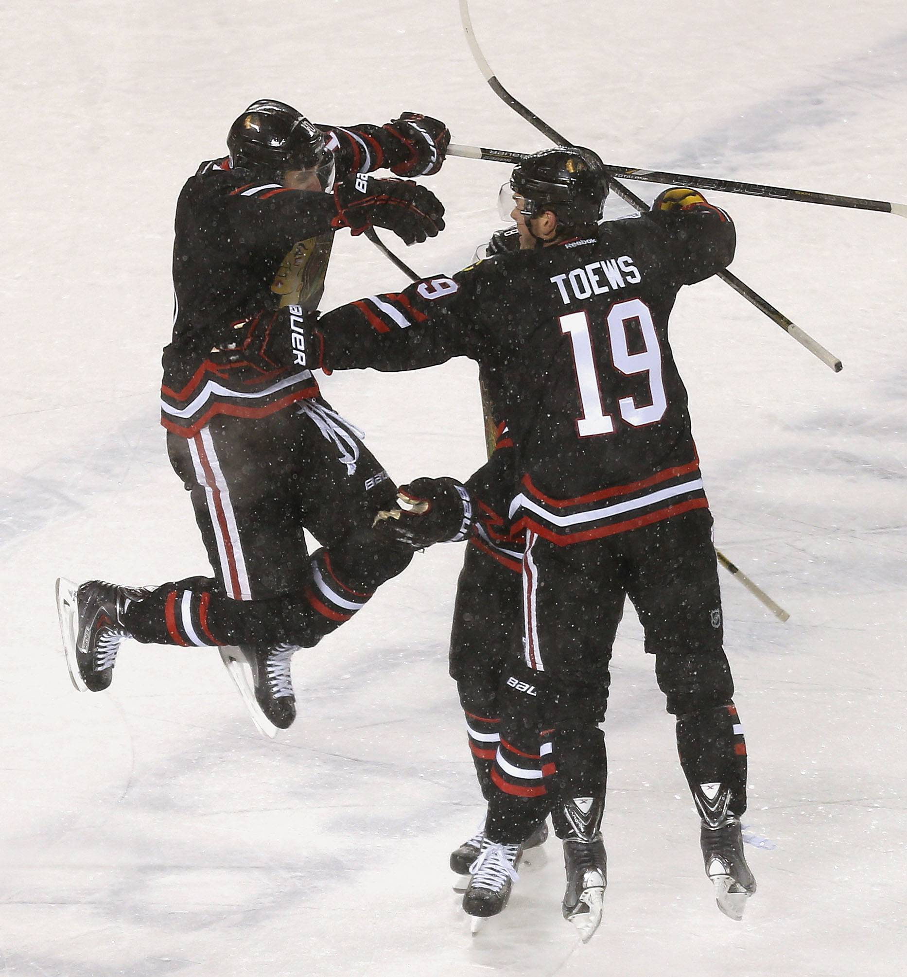 Chicago Blackhawks left wing Patrick Sharp, left, jumps into the arms of Chicago Blackhawks center Jonathan Toews after scoring against the Pittsburgh Penguins Saturday at Soldier Field.