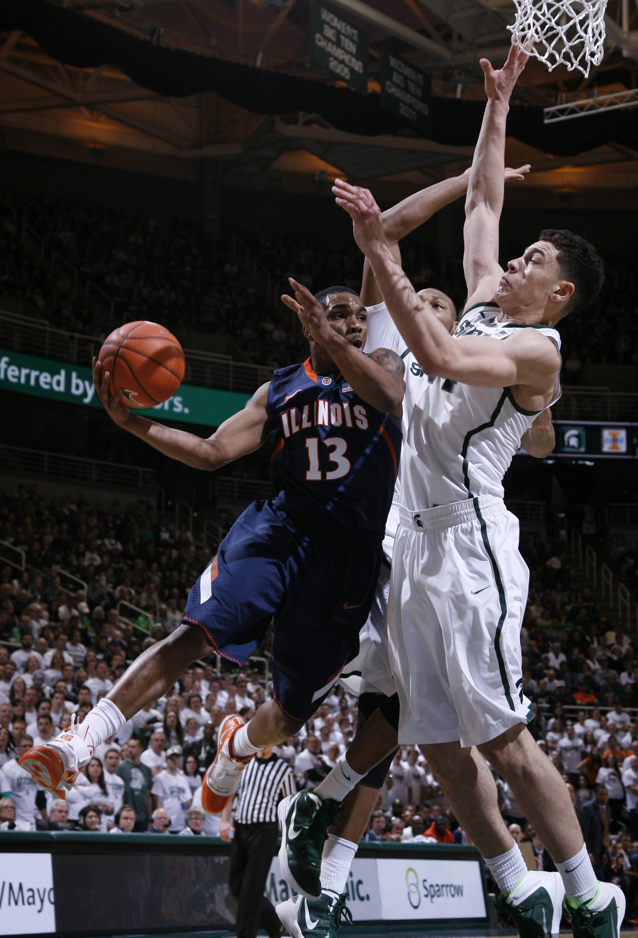 Illinois' Tracy Abrams (13) dishes off against Michigan State's Gavin Schilling, right, and Adreian Payne during Saturday's game in East Lansing. Abrams scored 12 points, leading the Illini to a 53-46 win over Michigan State.