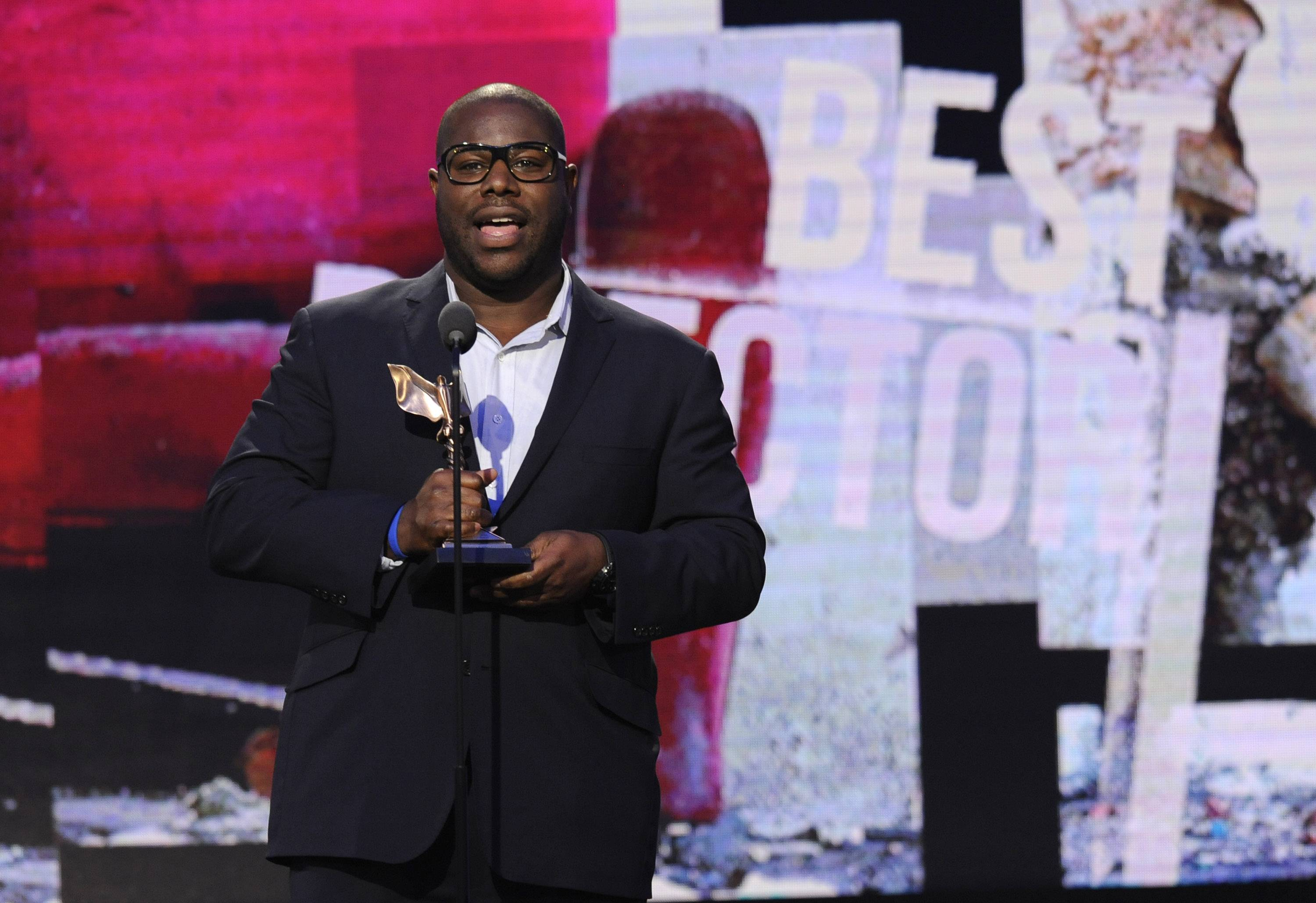 "Steve McQueen accepts the award for best director for ""12 Years a Slave"" on stage at the 2014 Film Independent Spirit Awards, on Saturday in Santa Monica, Calif."