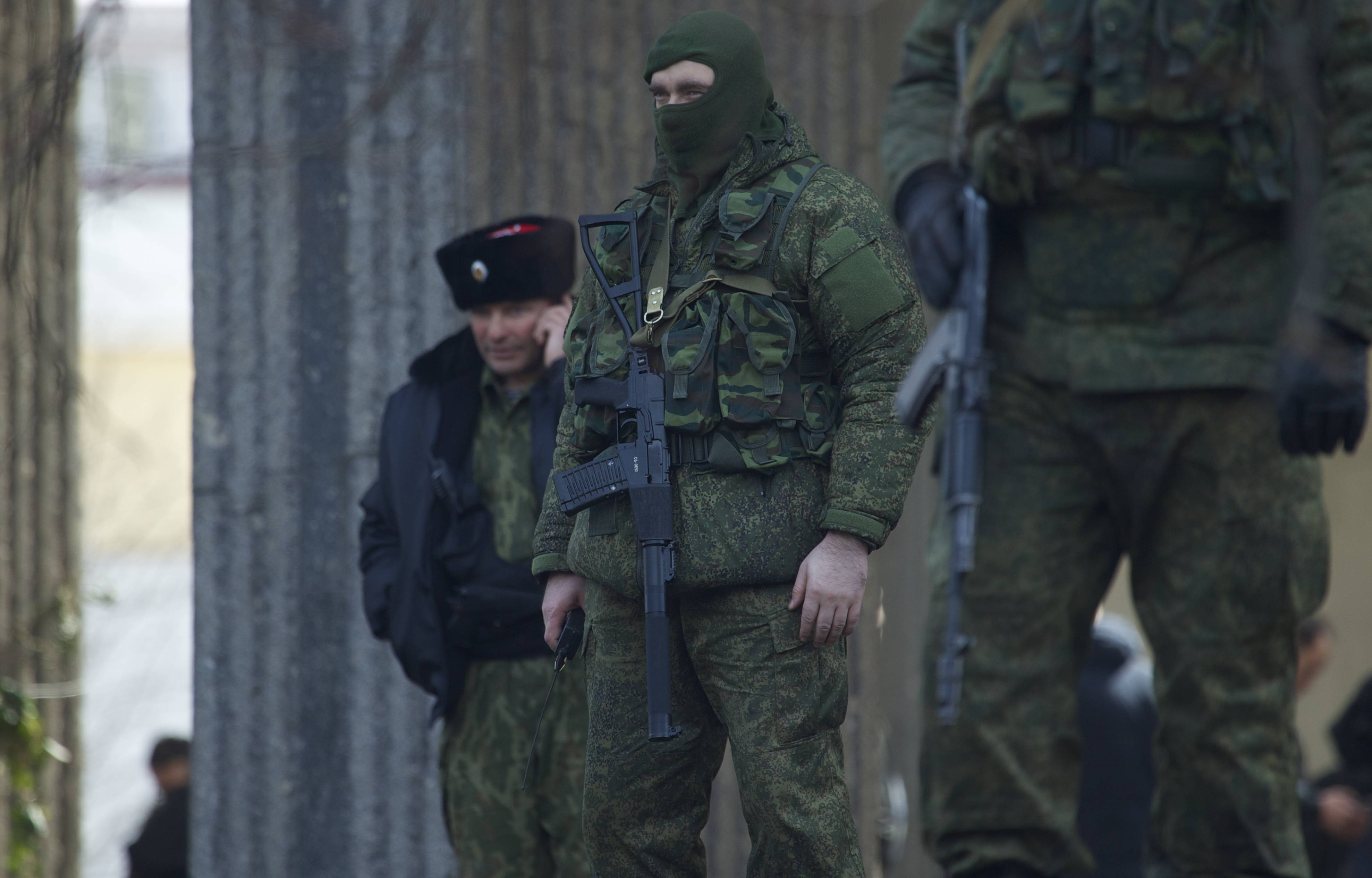 Unidentified gunmen wearing camouflage uniforms block the entrance of the Crimean Parliament building Saturday in Simferopol, Ukraine.