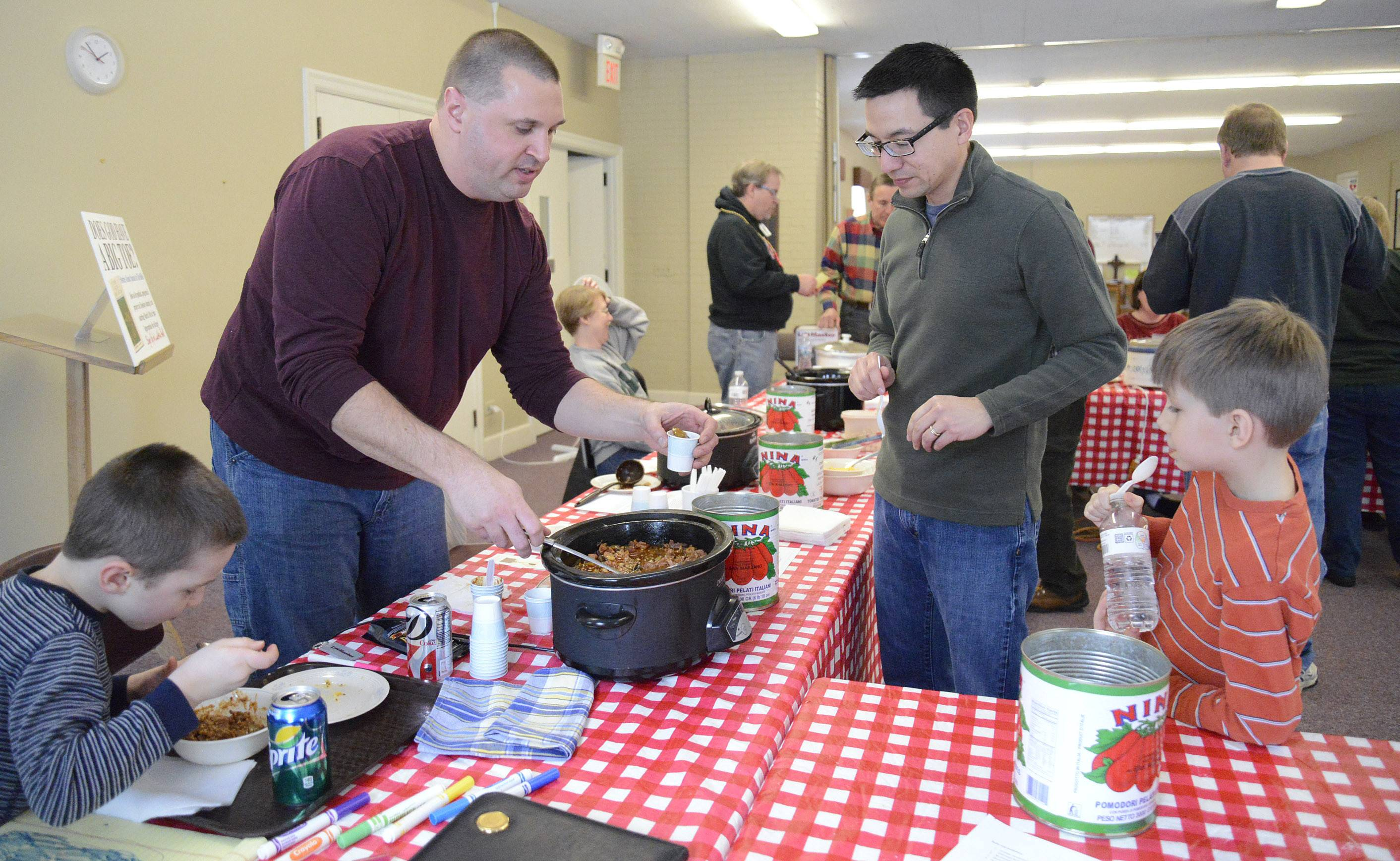 "Rob Ulaszek of St. Charles scoops out a taste of his ""Smokey the Bear Chili/Green Chili Pork Stew"" to Erik Balisi of Batavia and his son, Eli, 9, at St. Charles Episcopal Church's chili cook-off Saturday, March 1. Ulaszek's son, Oliver, 4, left, noshes on his dad's chili which took first place. Ulaszek's wife, Lisel, took third place."