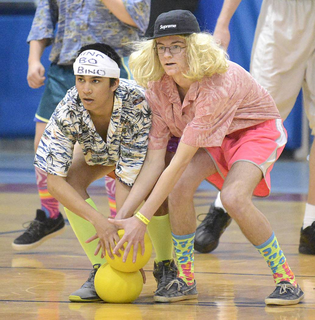 Members of team Tropic Thunder Nick Bernardino of Cary, left, and Peyton Day of East Dundee, both 17, scoop up balls to whip at The Ball Dodgers team during Carpentersville IAFF Local 4790's fourth annual dodgeball tournament Saturday at Dundee-Crown High School in Carpentersville.
