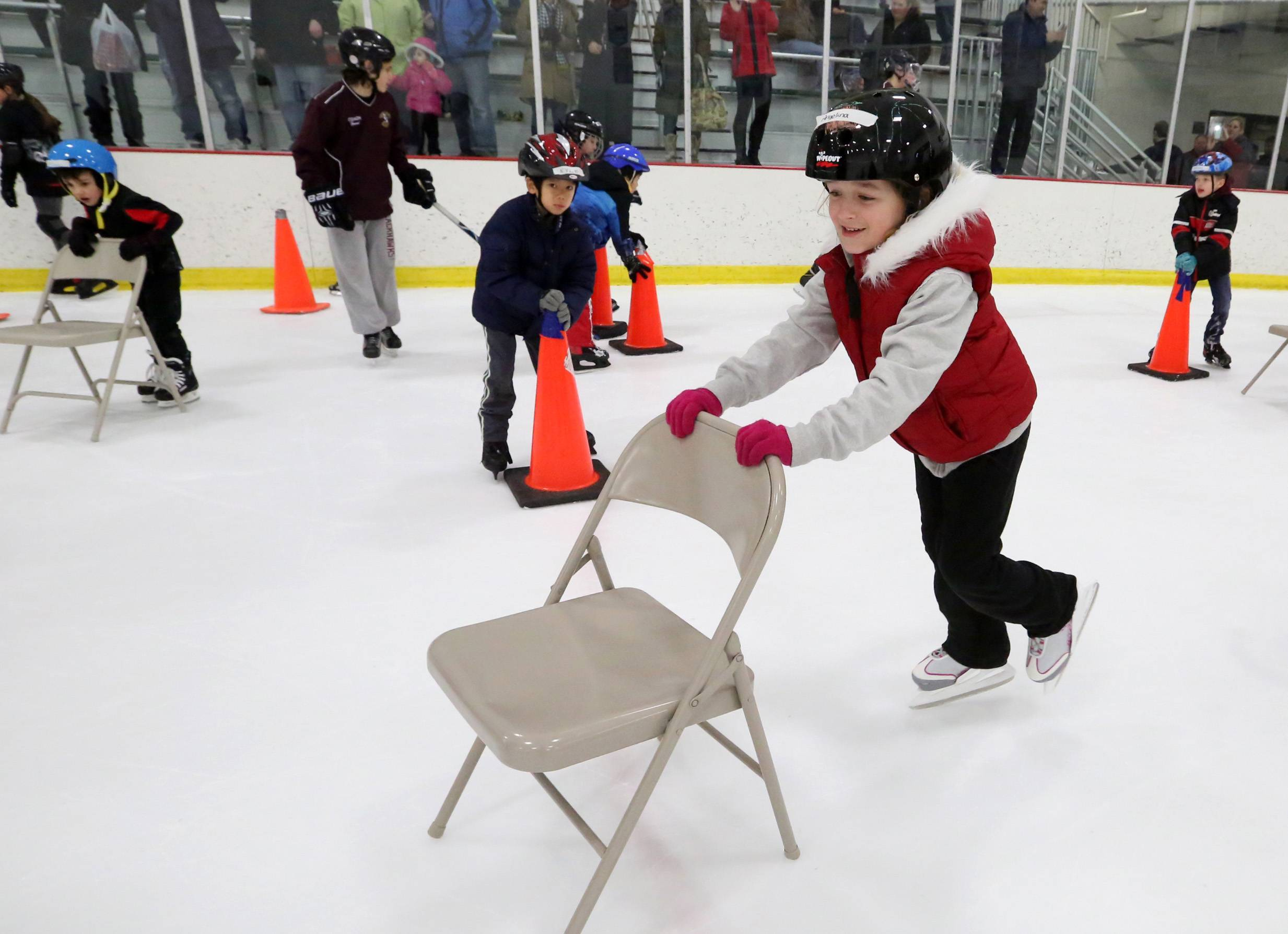 Angelina Sadowski, 6, of Streamwood, learns to stay up on her skates using a folding chair at USA Hockey's annual Try Hockey For Free event at the Triphahn Center on Saturday in Hoffman Estates.