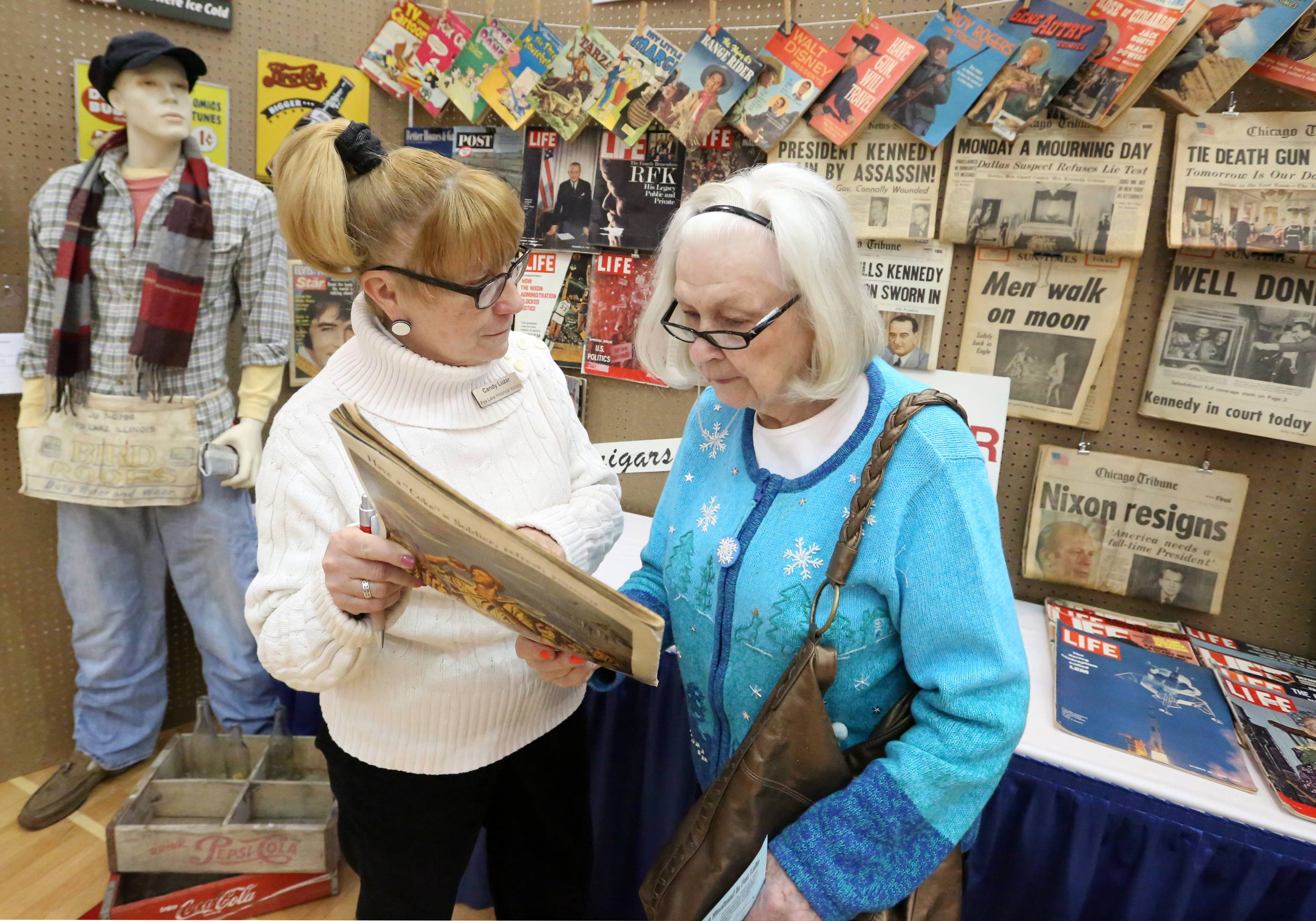 Candy Luzar with the Fox Lake Historical Society, left, compares old newspapers with a current one with Maryann Osikowicz of Fox Lake at the society's booth at Fox Lake Business & Family Expo at Grant High School on Saturday in Fox Lake.