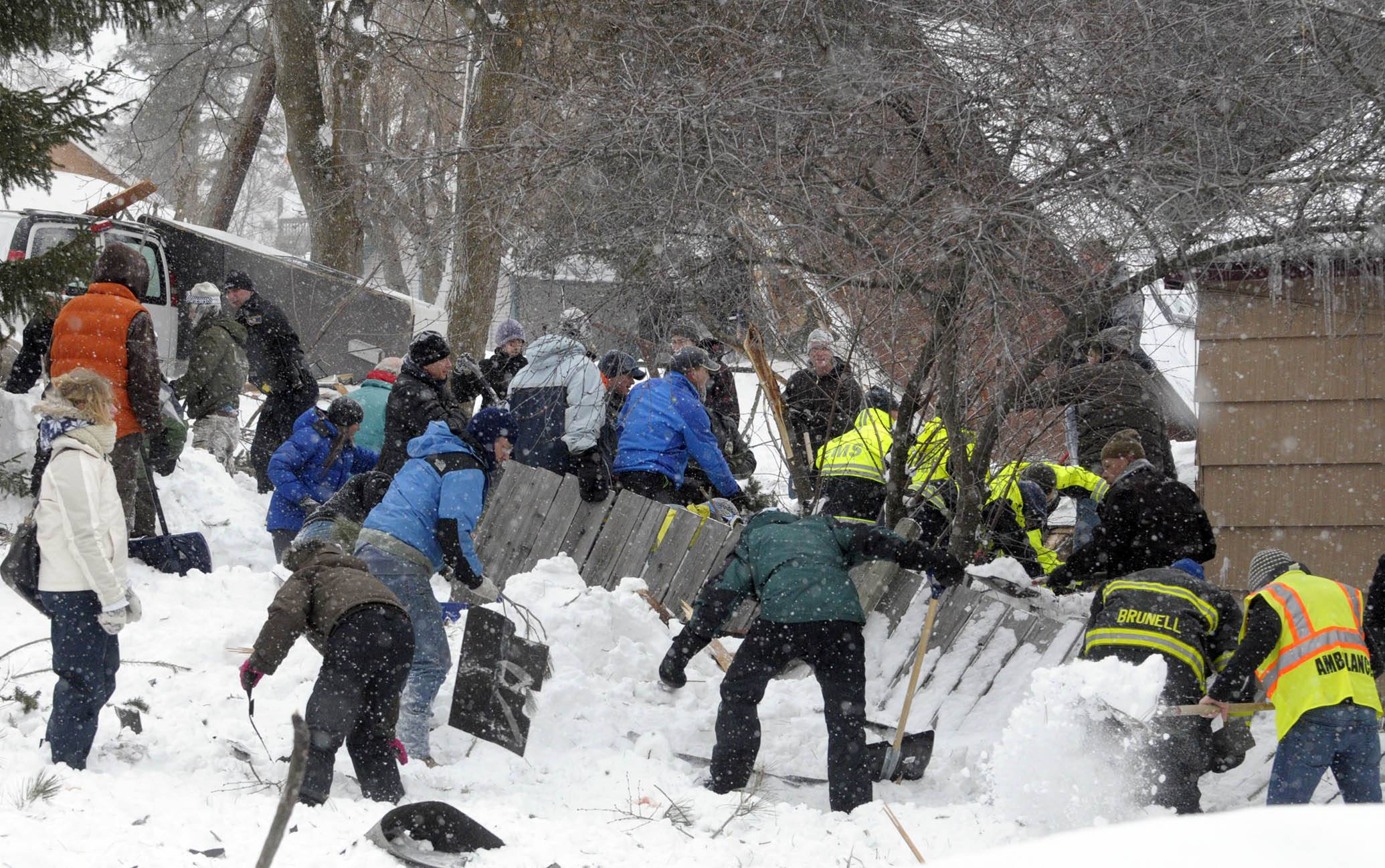 Rescuers look for a boy buried in the snow. The avalanche roared into a residential neighborhood and destroyed a house, but three people were found alive.