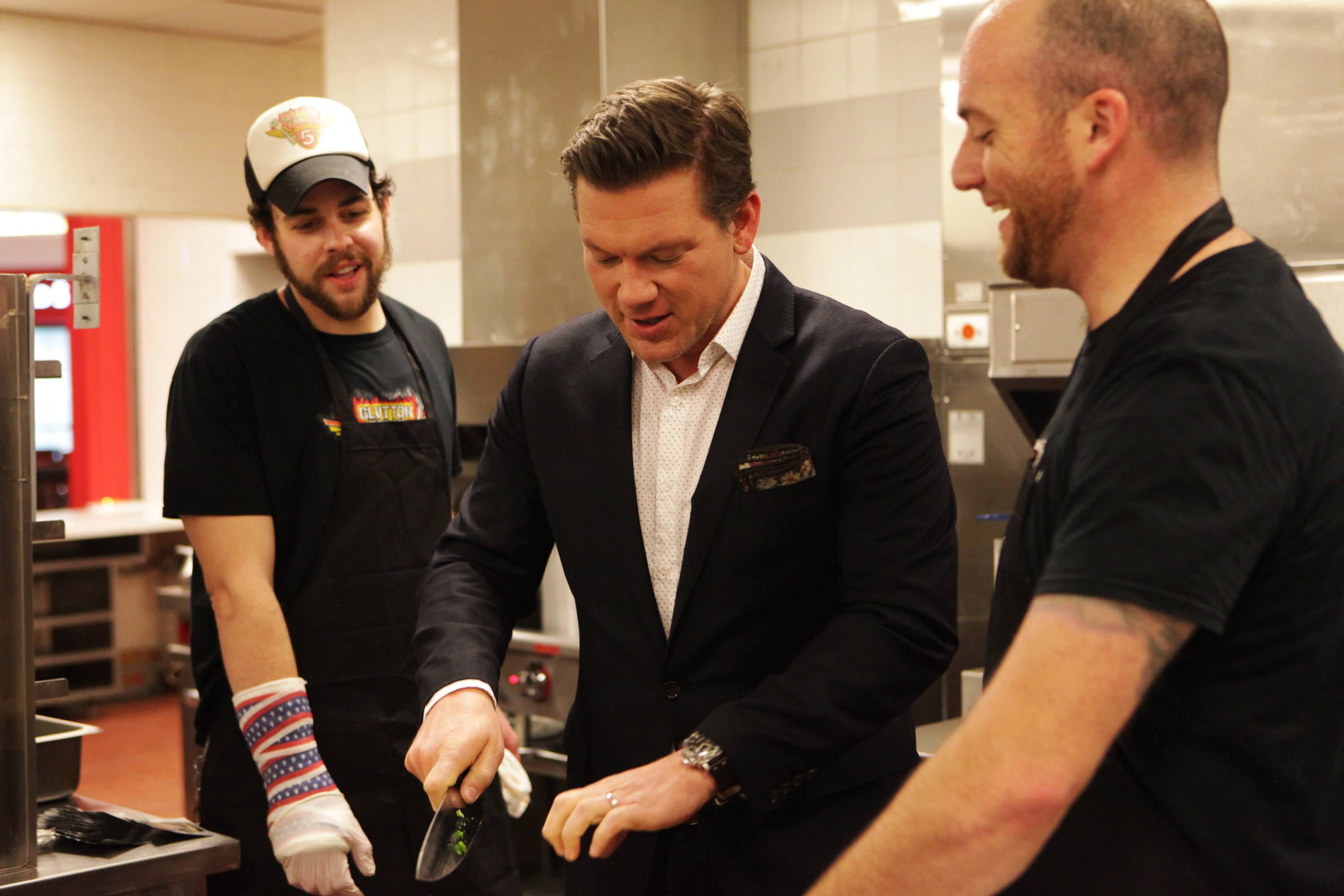 "Tyler Florence, host of ""Food Court Wars,"" teaches the ""Glutton Force 5"" team of Tim ""Gravy"" Brown, right, and Patrick ""Deep Dish"" Bertoletti, how to use a kitchen knife while preparing their signature ""tacos in a bag"" meal for 25 dinners. Brown and Bertoletti are both competitive eaters based in Chicago, and Brown grew up in Barrington. They will be featured on Sunday's episode of ""Food Court Wars,"" which airs on the Food Network."