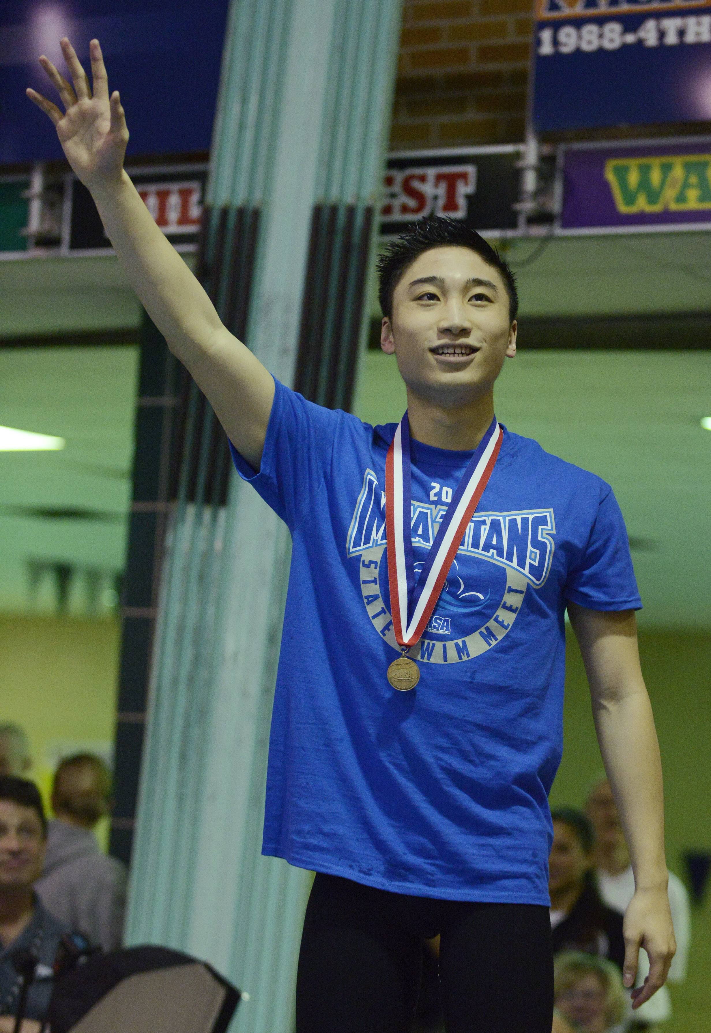 Steven Tan of Illinois Math and Science Academy waves from the award stand after finishing first in the 100-yard butterfly at state Saturday.
