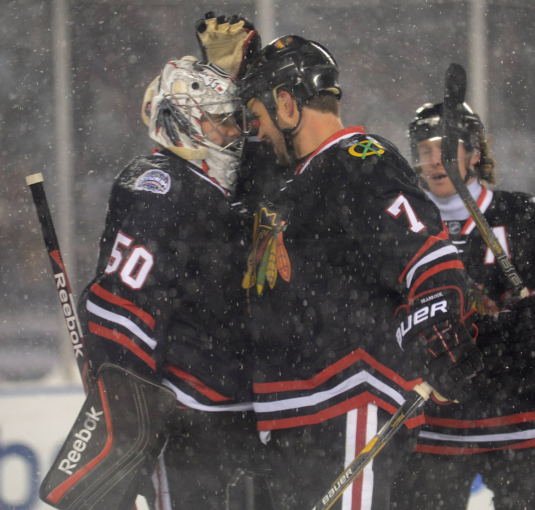 Chicago Blackhawks goalie Corey Crawford is congratulated by Chicago Blackhawks defenseman Brent Seabrook at the end of Saturday's Coors Light Stadium Series game at Soldier Field between the Blackhawks and Pittsburgh Penguins.
