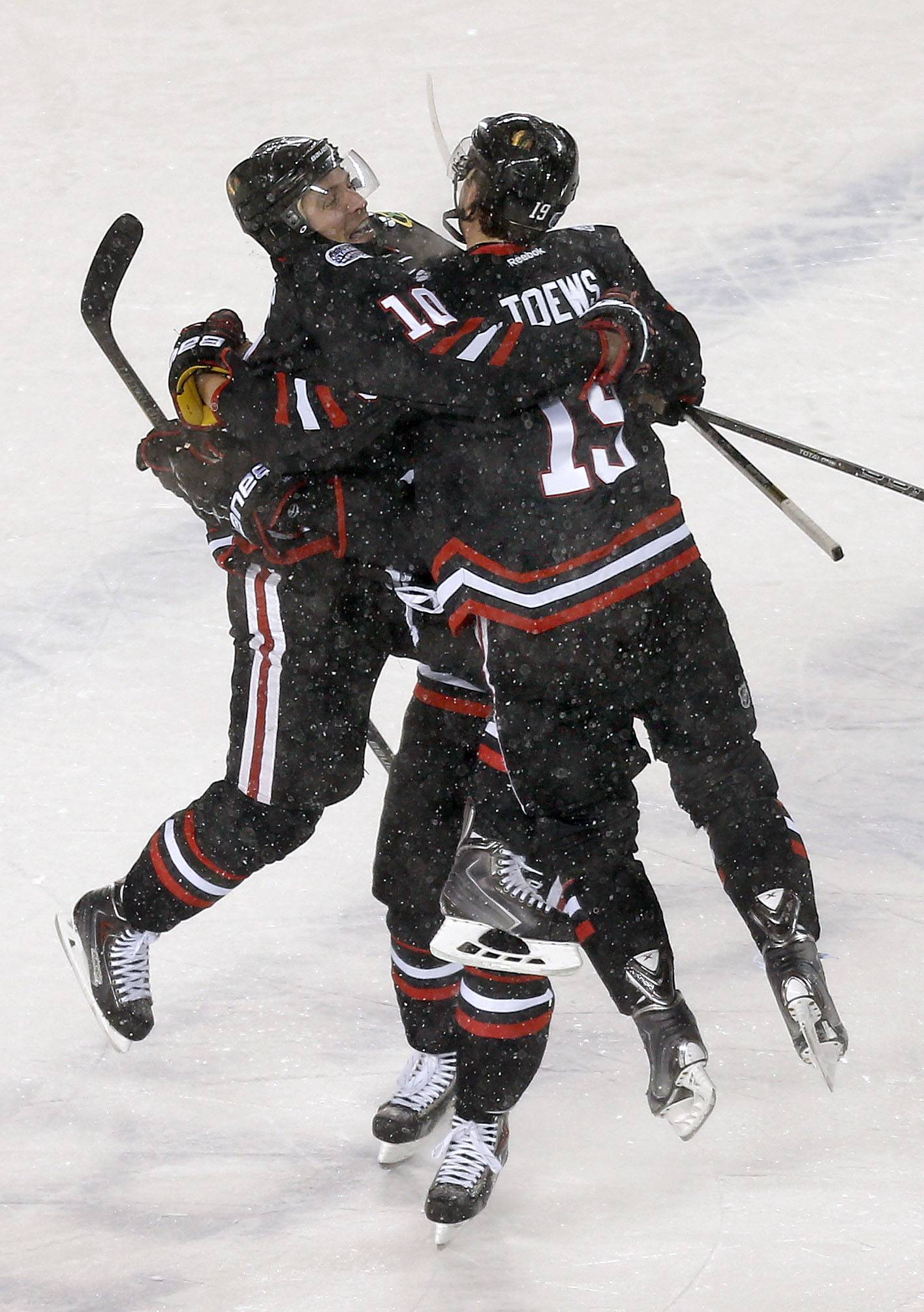 Chicago Blackhawks left wing Patrick Sharp, left, jumps into the arms of Chicago Blackhawks center Jonathan Toews after scoring in the first period during the NHL Stadium Series between the Blackhawks and the Penguins Saturday at Soldier Field.