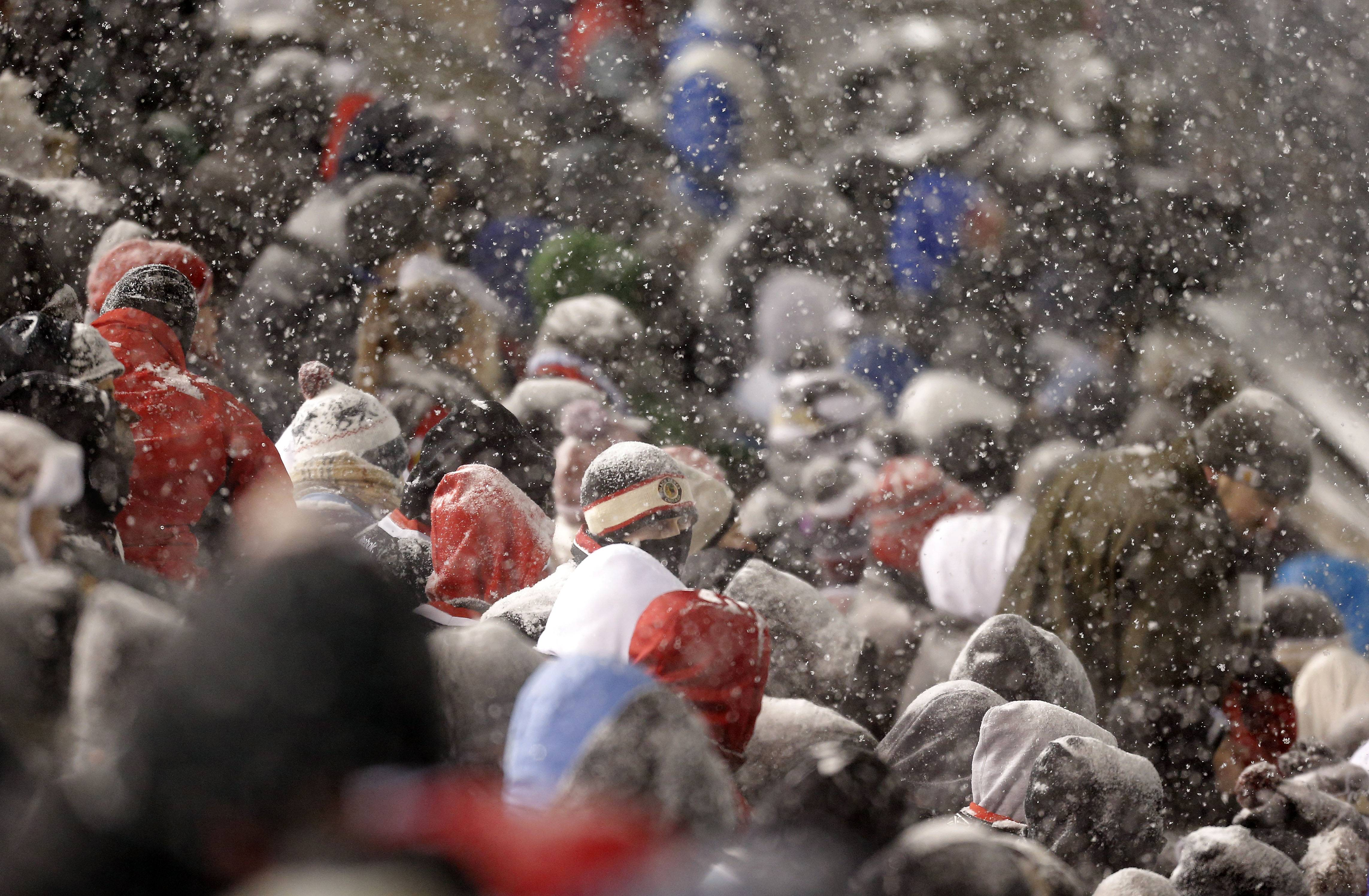 Snow covers fans during the NHL Stadium Series between the Blackhawks and the Penguins Saturday at Soldier Field.