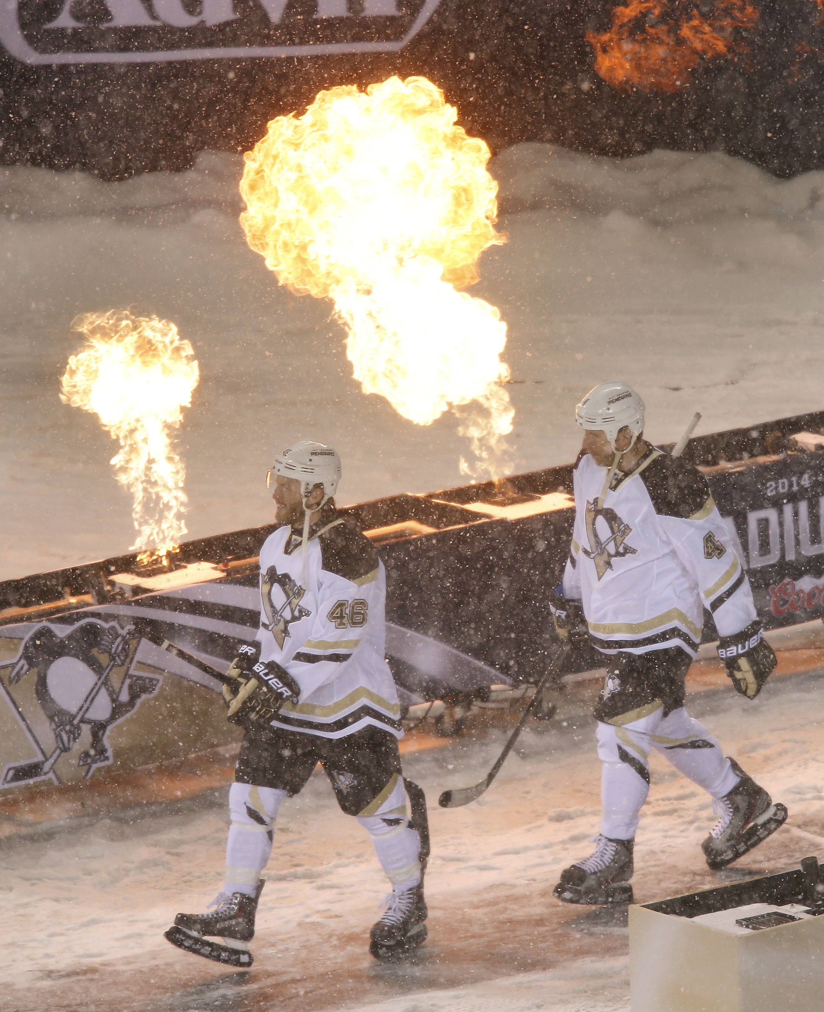 Penguins players enter the ice during NHL Stadium Series between the Blackhawks and the Penguins Saturday at Soldier Field.