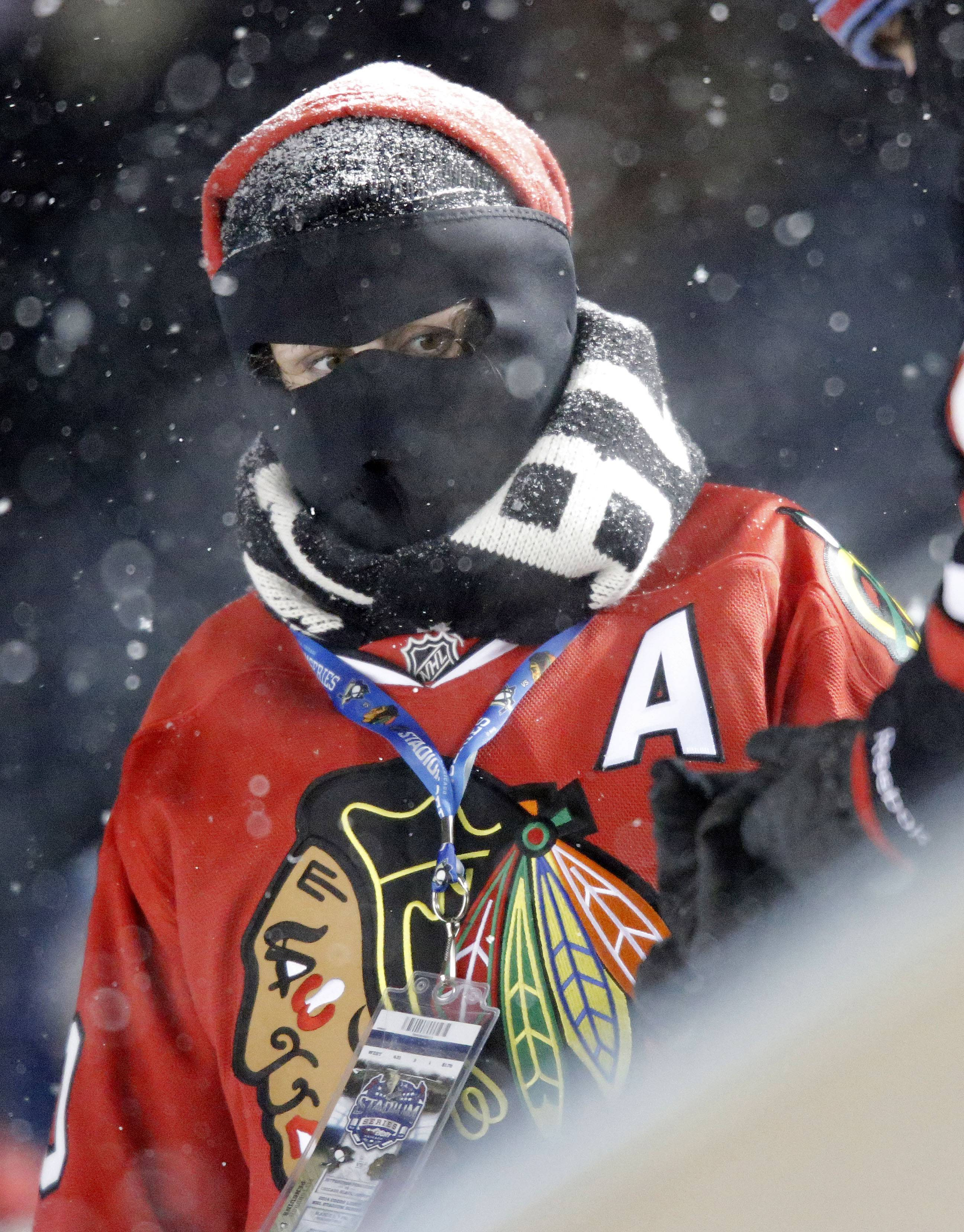 Fans cover from the bitter cold during the NHL Stadium Series between the Blackhawks and the Penguins Saturday at Soldier Field.