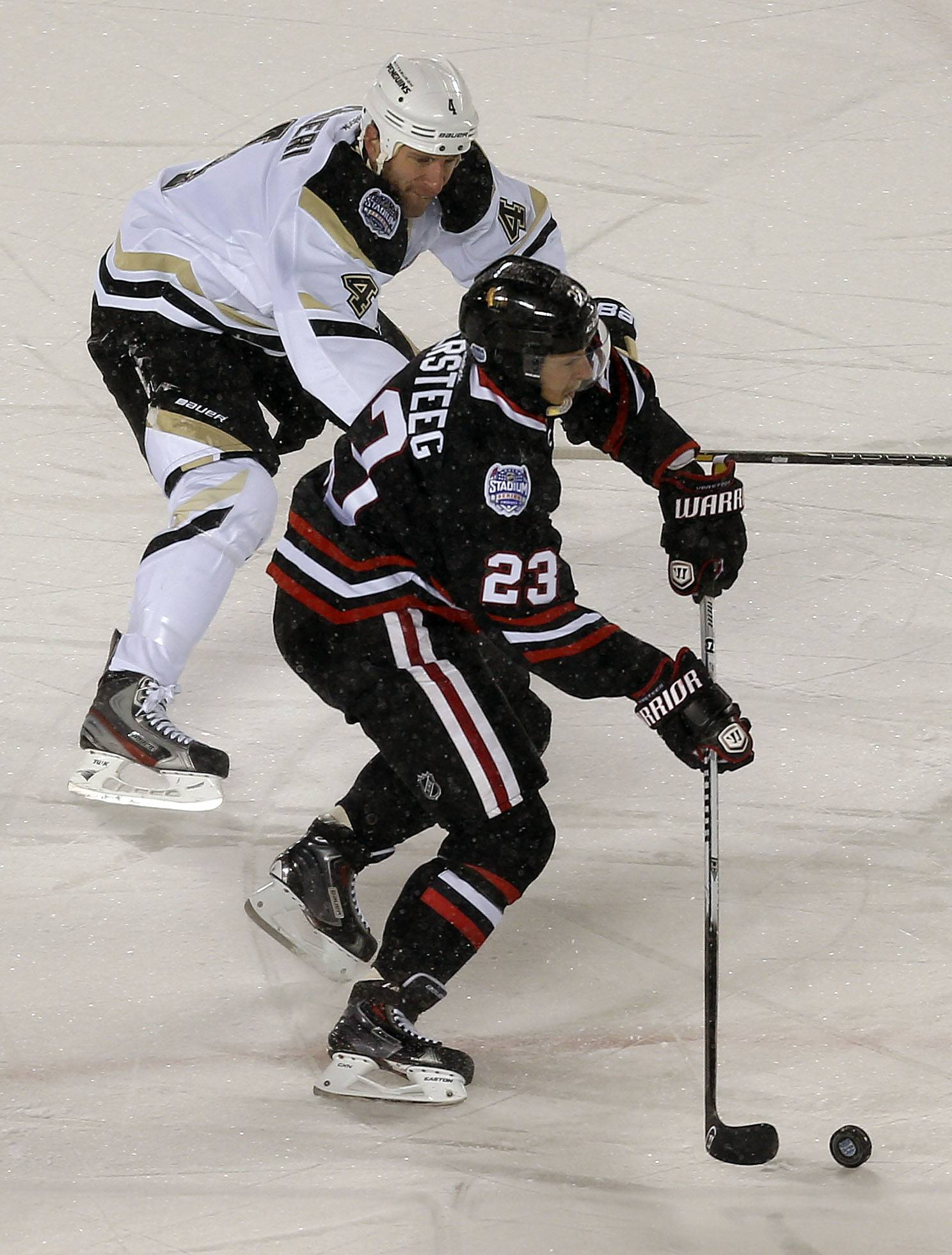 Chicago Blackhawks right wing Kris Versteeg drives on Pittsburgh Penguins Rob Scuderi during the NHL Stadium Series between the Blackhawks and the Penguins Saturday at Soldier Field.